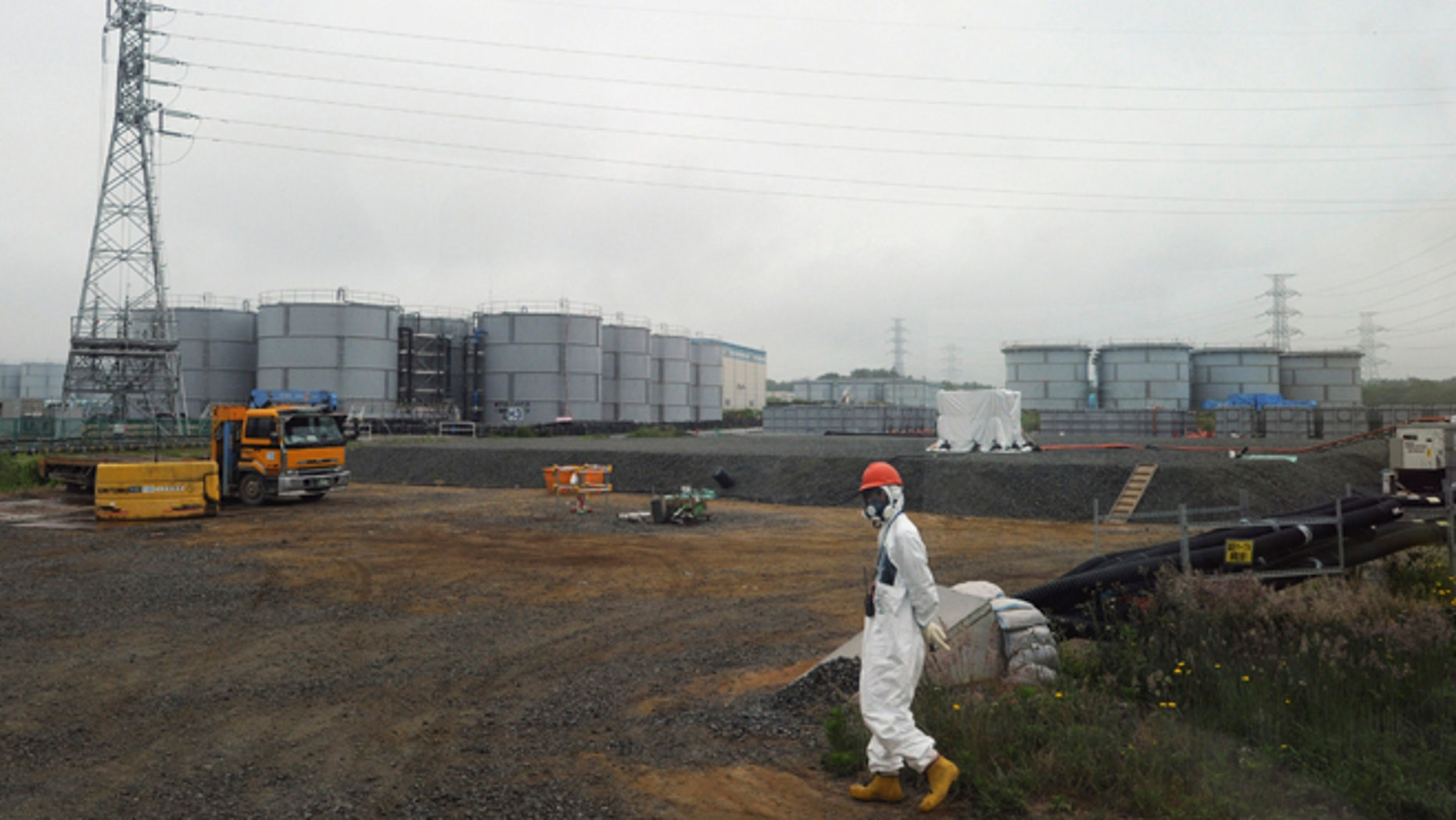 June 12, 2013: In this file photo, a construction worker walks beside the underground water tanks at the Fukushima Dai-ichi nuclear plant at Okuma in Fukushima prefecture, Japan. The operator of Japan's tsunami-crippled nuclear power plant said Tuesday, Aug. 20, 2013, that about 300 tons of highly radioactive water have leaked from one of the hundreds of storage tanks there - its worst leak yet from one of the vessels.