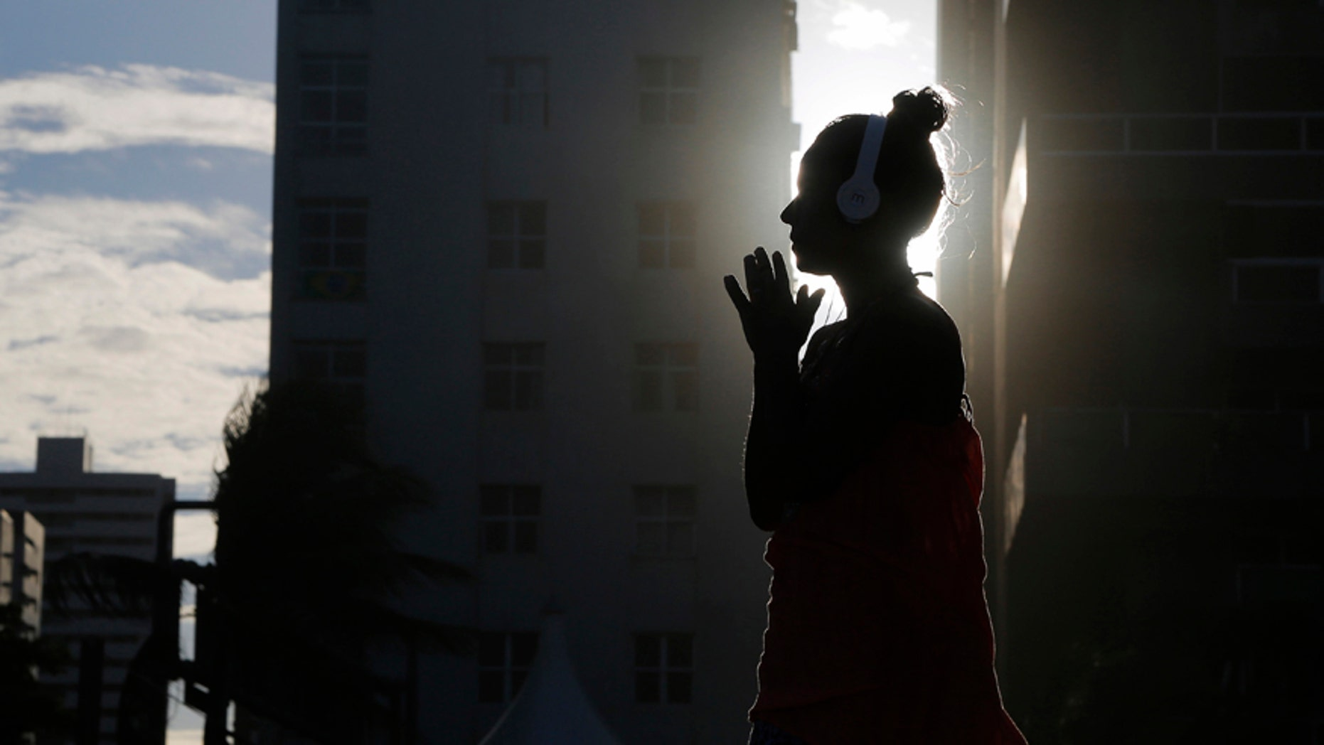File photo: A woman listens to music as the sun sets as seen between buildings on Boa Viagem beach in Recife June 30, 2014.