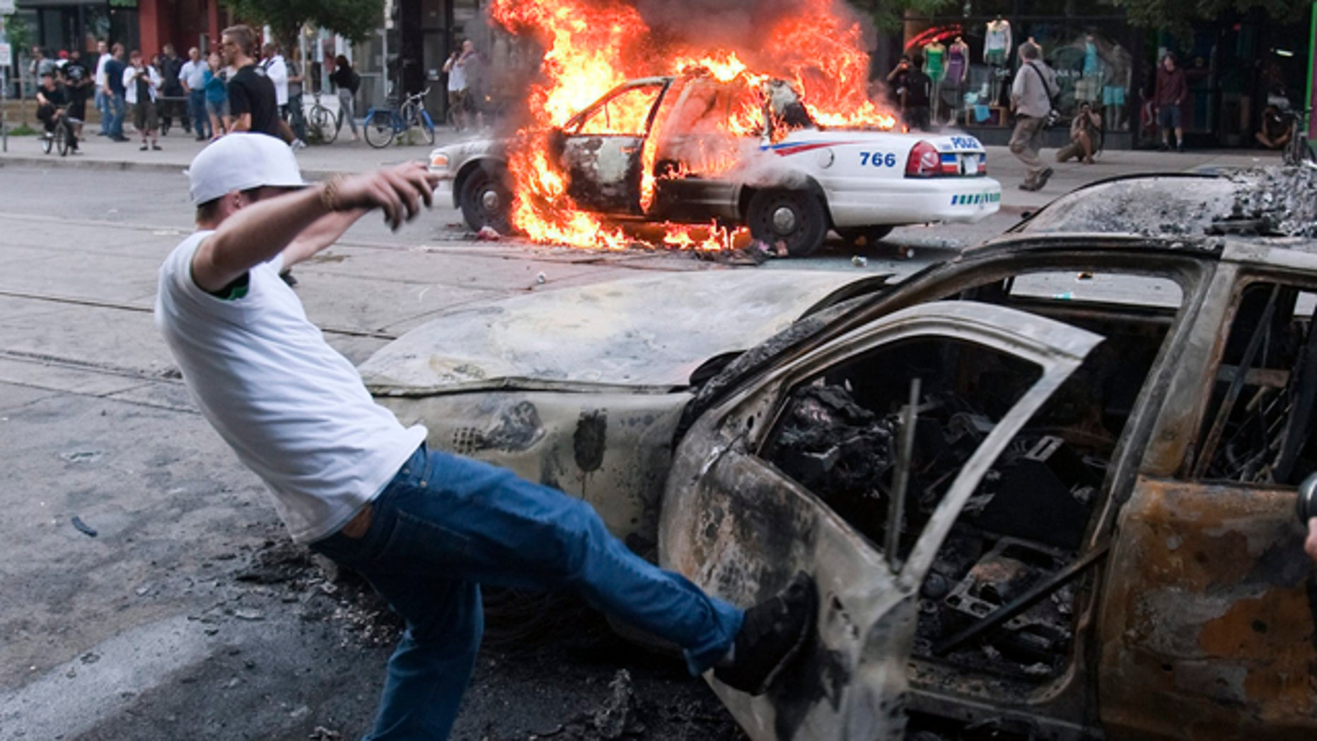 June 26: A protester kicks a burnt-out car as a police vehicle burns in the background during an anti-G-20 demonstration in Toronto. (AP Photo/The Canadian Press, Ryan Remiorz)