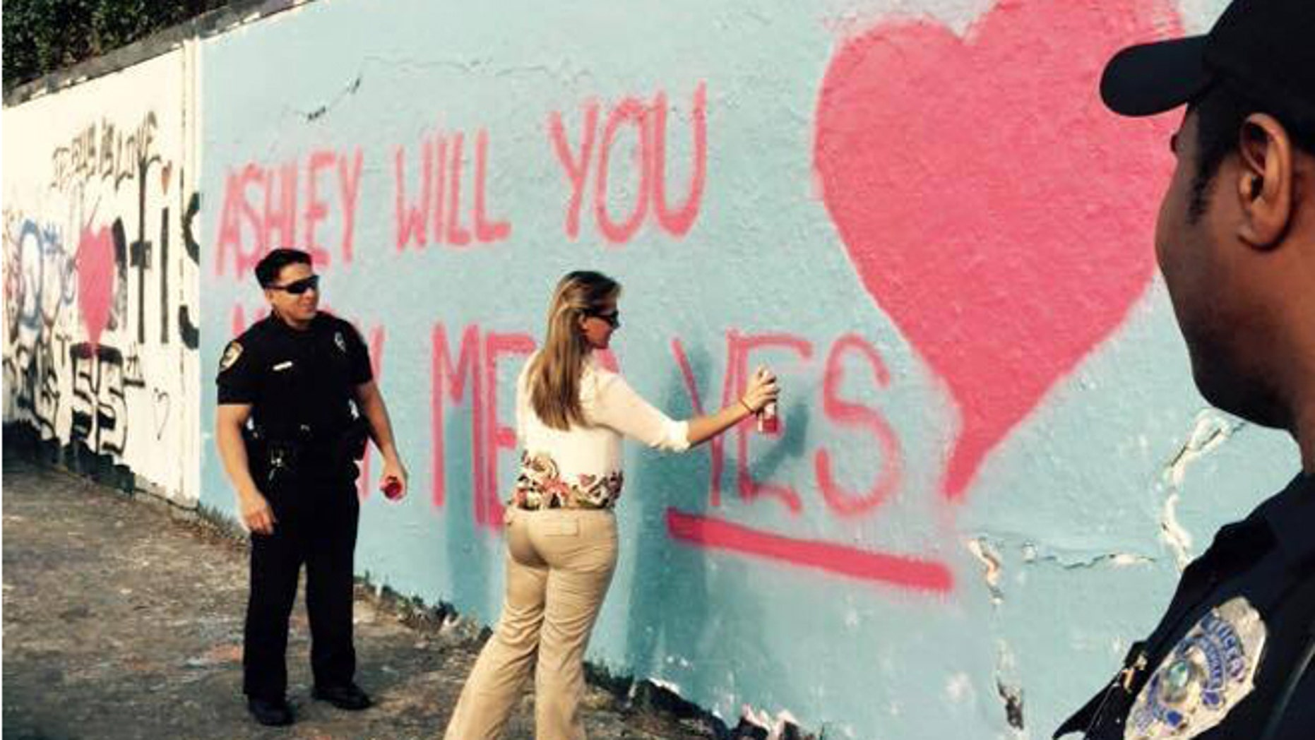 Officer Christian Hickey proposes to girlfriend Ashley Alderman at Gainesville, Fla., 34th Street graffiti wall. (Gainesville Police Department)