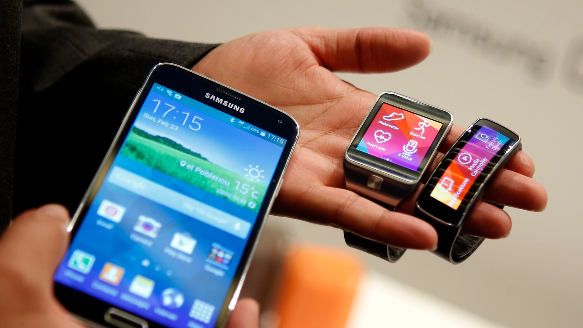 The Samsung Galaxy S5 smartphone (L), Gear 2 smartwatch (C) and Gear Fit fitness band are displayed at the Mobile World Congress in Barcelona.