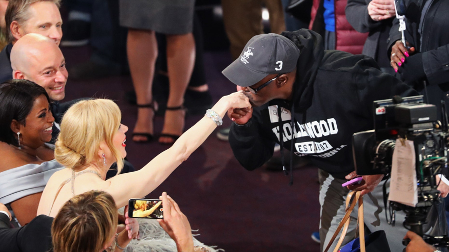 """""""Gary from Chicago"""" kisses the hand of actor Nicole Kidman during a skit at the 89th Annual Academy Awards."""