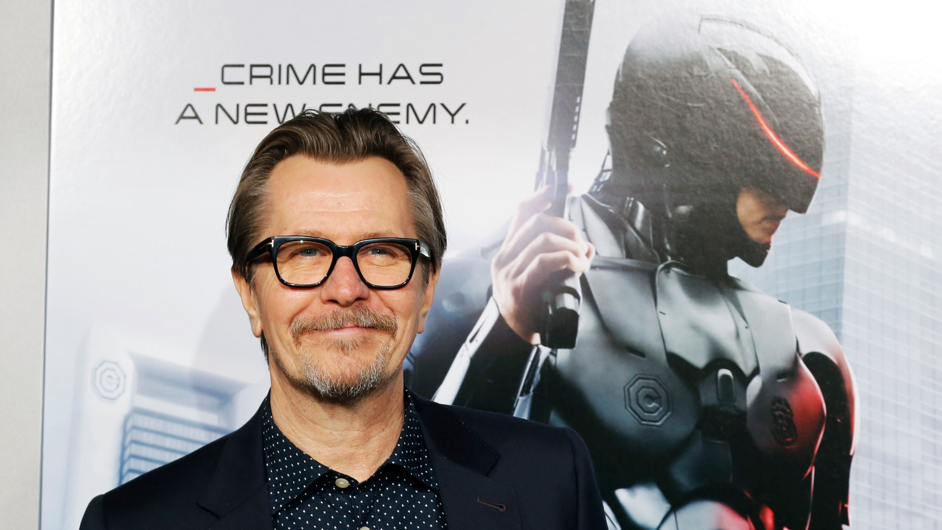 """Actor Gary Oldman one of the stars of film """"Robocop"""" arrive for the film's premiere in Hollywood, California February 10, 2014. REUTERS/Fred Prouser (UNITED STATES - Tags: ENTERTAINMENT PROFILE) - RTX18KF4"""