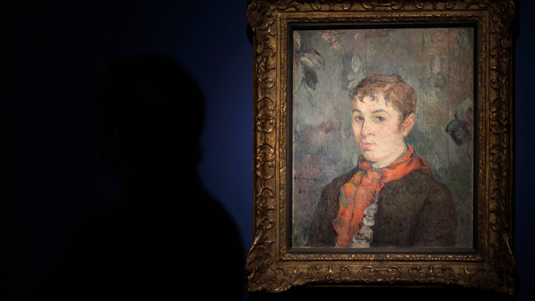 """File photo - A man stands next to the painting """"The boss's daughter"""" by French painter Paul Gauguin during a media presentation of the art exhibition """"Paul Gauguin, the dream of Panama"""" at the Interoceanic Canal Museum in Panama city December 6, 2012. (REUTERS/Carlos Jasso)"""