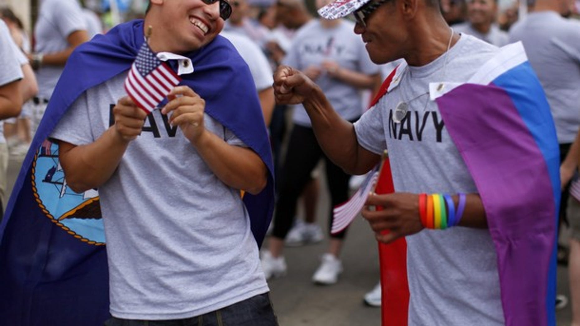 Matthew Avila (L), active duty gunners mate 2nd class U.S. Navy, receives a punch in the arm from former EN2 U.S. Navy's Ray Cordero as they prepare to march with active and non-active U.S. military personnel who are participating for the first time in San Diego's Gay Pride Parade in San Diego, July 16, 2011.
