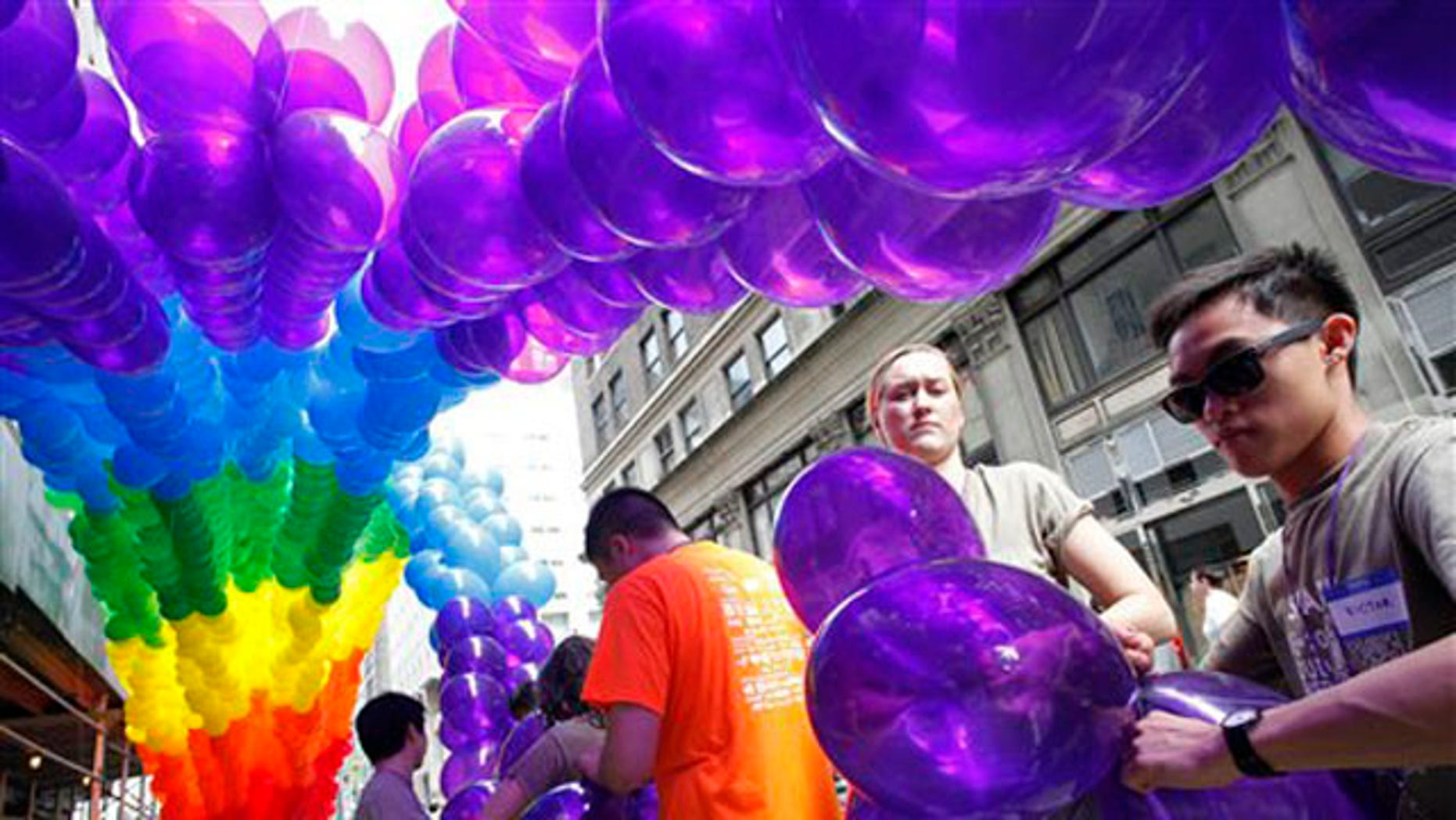 Kajsa Westman, second from right, of Stockholm, Sweden, and Victor Ng, right, of Seattle, tie balloons to a banner in preparation for the annual Gay Pride parade, Sunday, June 26, 2011 in New York. One of the world's oldest and largest gay pride parades was expected to become a victory celebration Sunday after New York's historic decision to legalize same-sex marriage.  The law signed by Gov. Andrew Cuomo on Friday doesn't take effect for 30 days. (AP Photo/Mark Lennihan)