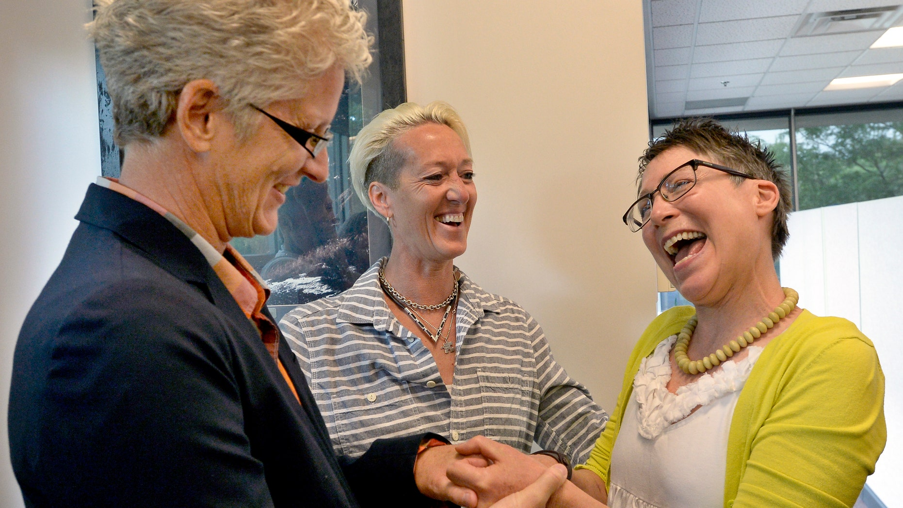 July 1, 2014: Julie Hoehing, left, and Nancy Cooley, right, laugh after friend Dana Derichsweiler, middle, performed a marriage ceremony at the Boulder County Clerk and Recorder'ss Office in Boulder, Colo.