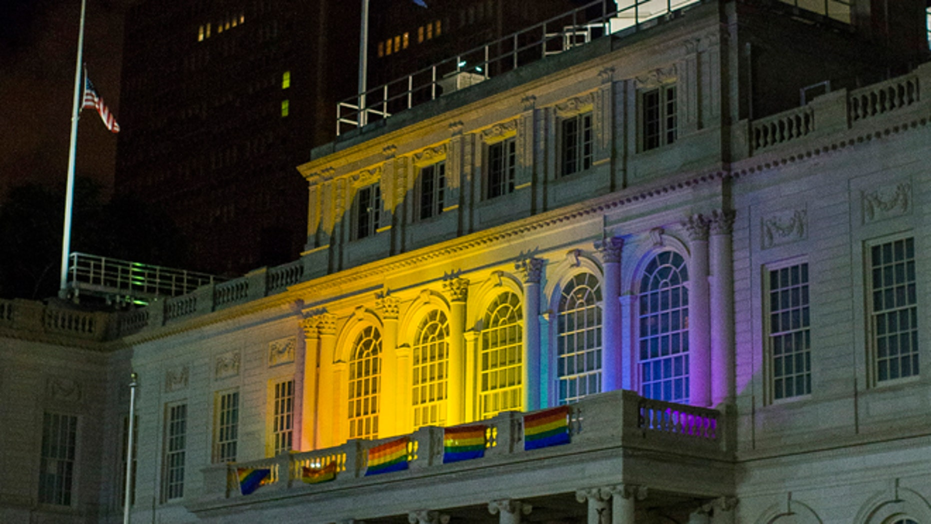 June 12, 2016: The New York City Hall building is illuminated in the colors of the LGBT pride flag in honor of the victims of the mass shooting in Orlando, Florida, in New York.