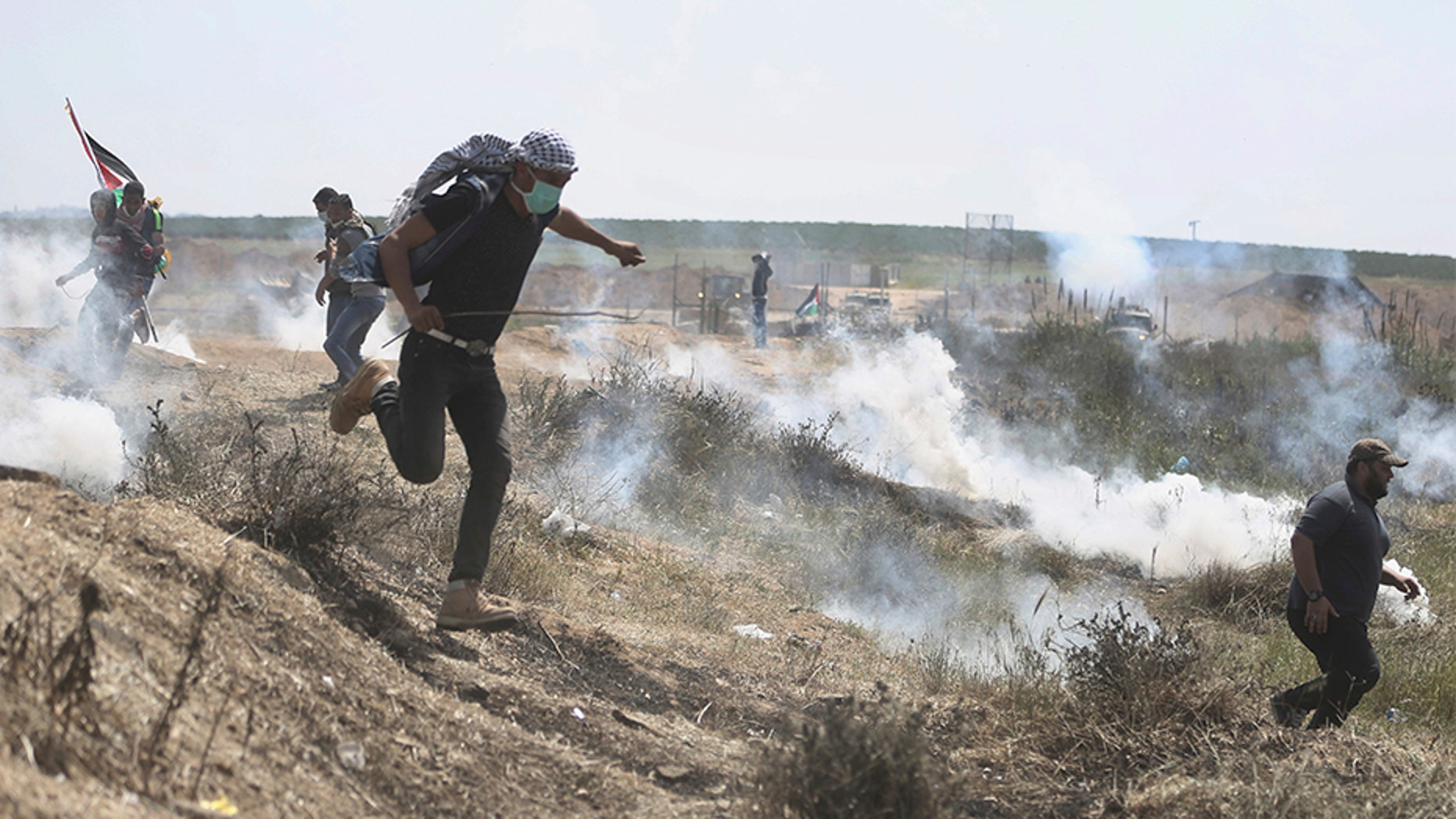 April 6, 2018: Palestinian protesters run for cover from teargas fired by Israeli troops during a protest at the Gaza Strip's border with Israel.