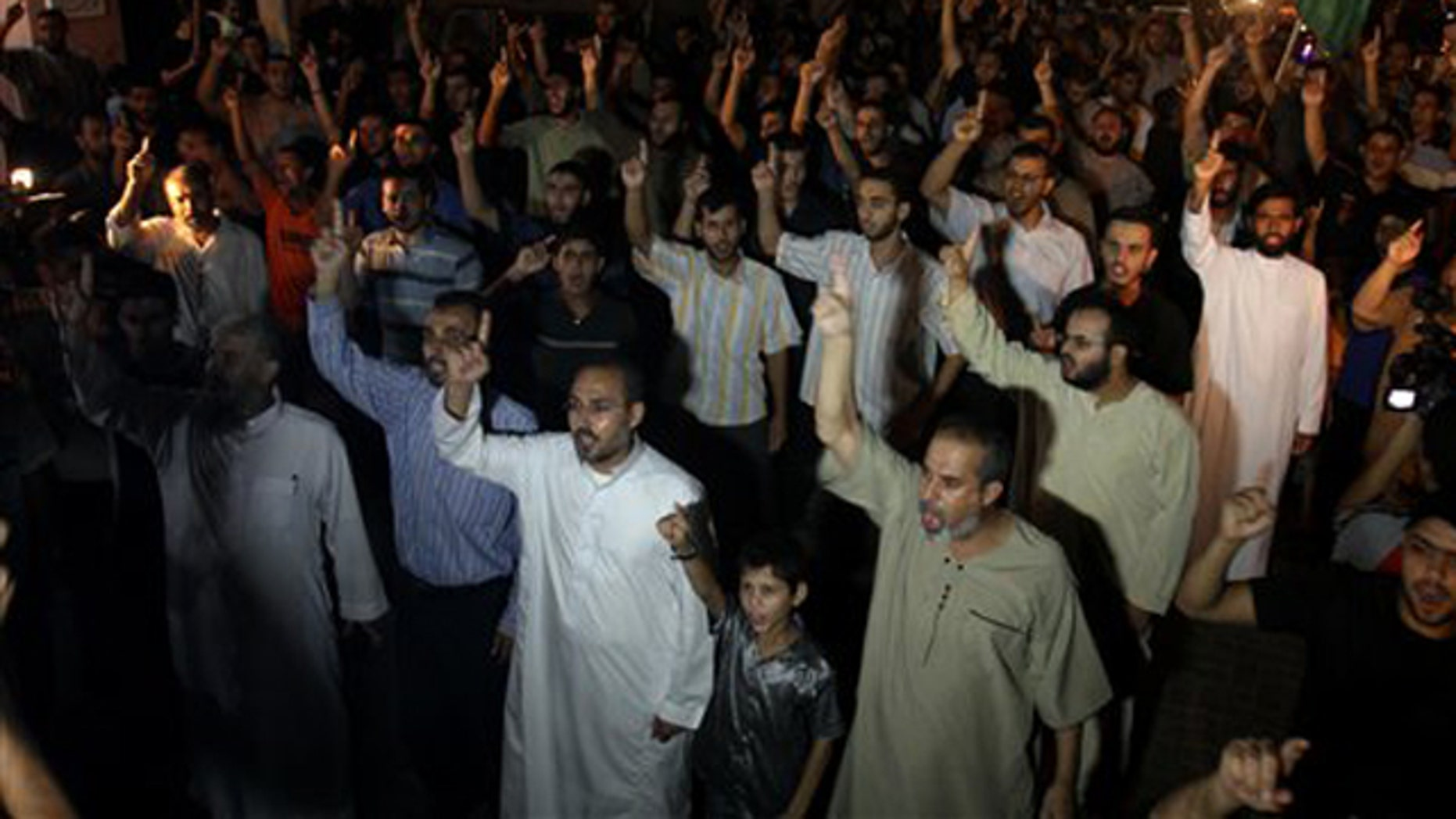 Palestinian supporters of Hamas raise their right index fingers in the air as a sign of loyalty to the group during a Gaza Strip rally to celebrate a militant attack in the southern West Bank Aug. 31. (AP Photo)