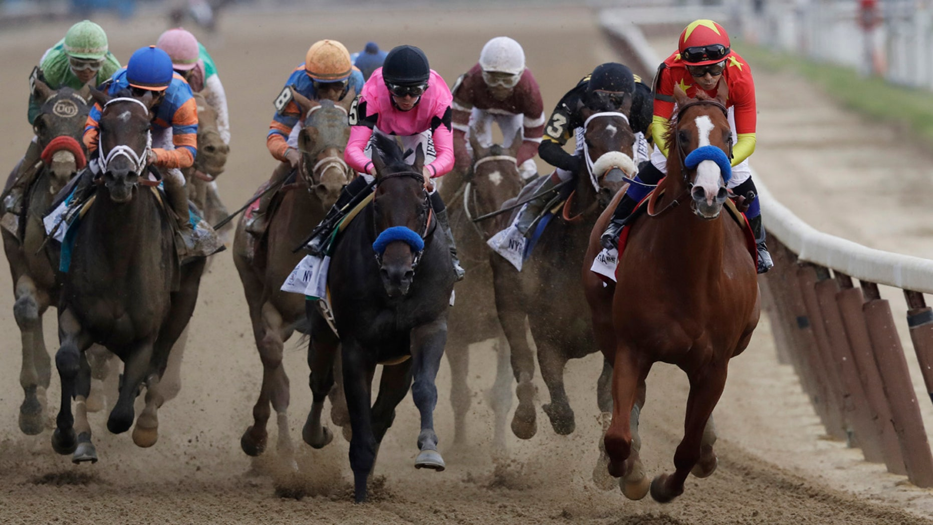 Justify, right, ridden Mike Smith leads the field at the end of the backstretch during the Belmont Stakes horse race.
