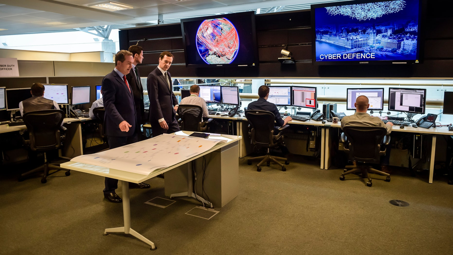 Britain's Chancellor of the Exchequer George Osborne is shown the 24 hour Operations Room inside GCHQ, by the Director of GCHQ Robert Hannigan (C) and Cheltenham MP Alex Chalk (L), in Cheltenham November 17, 2015. (REUTERS/Ben Birchall/Pool)