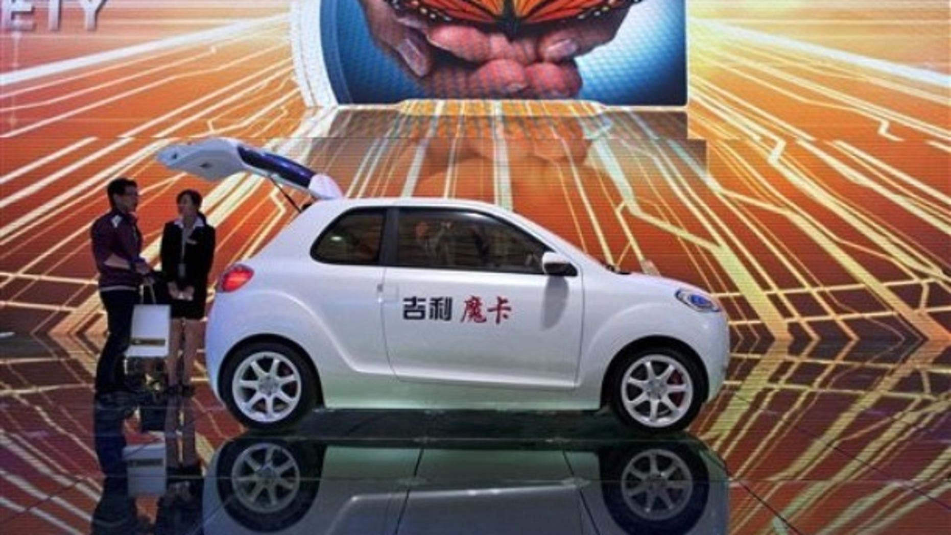 A woman chats with a visitor next to a Geely McCar displayed at the 14th Shanghai International Automobile Industry Exhibition in Shanghai, China Wednesday, April 20, 2011.
