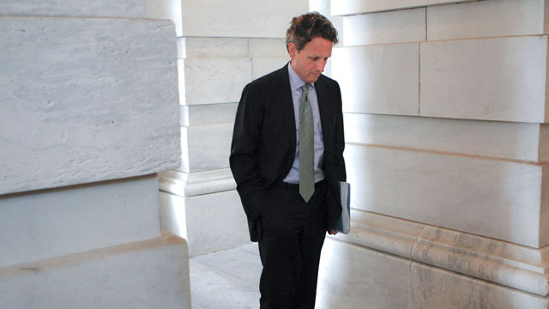 In this file photo taken June 16, 2011, Treasury Secretary Tim Geithner waits for the arrival of Vice President Joe Biden during the negotiations between Republicans and Democrats in Congress on how to solve America's debt crisis and budget problems, at the Capitol in Washington.