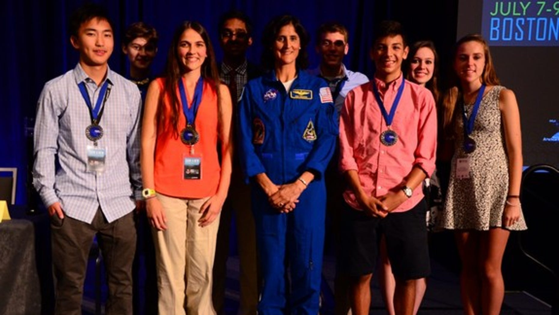 Anna-Sophia Boguraev, 16, of Bedford, New York, won the first ever Genes in Space contest for student experiments on the International Space Station. She can be seen here standing to the left of NASA astronaut Sunita Williams (center). They are