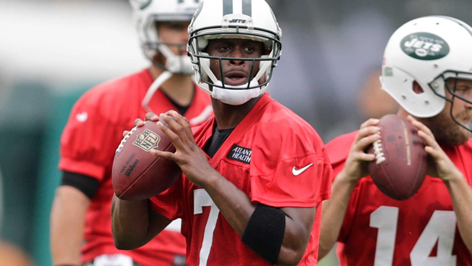 July 30, 2015: New York Jets quarterback Geno Smith, left, and quarterback Ryan Fitzpatrick, right, throw passes during drills at NFL football training camp in Florham Park, N.J.