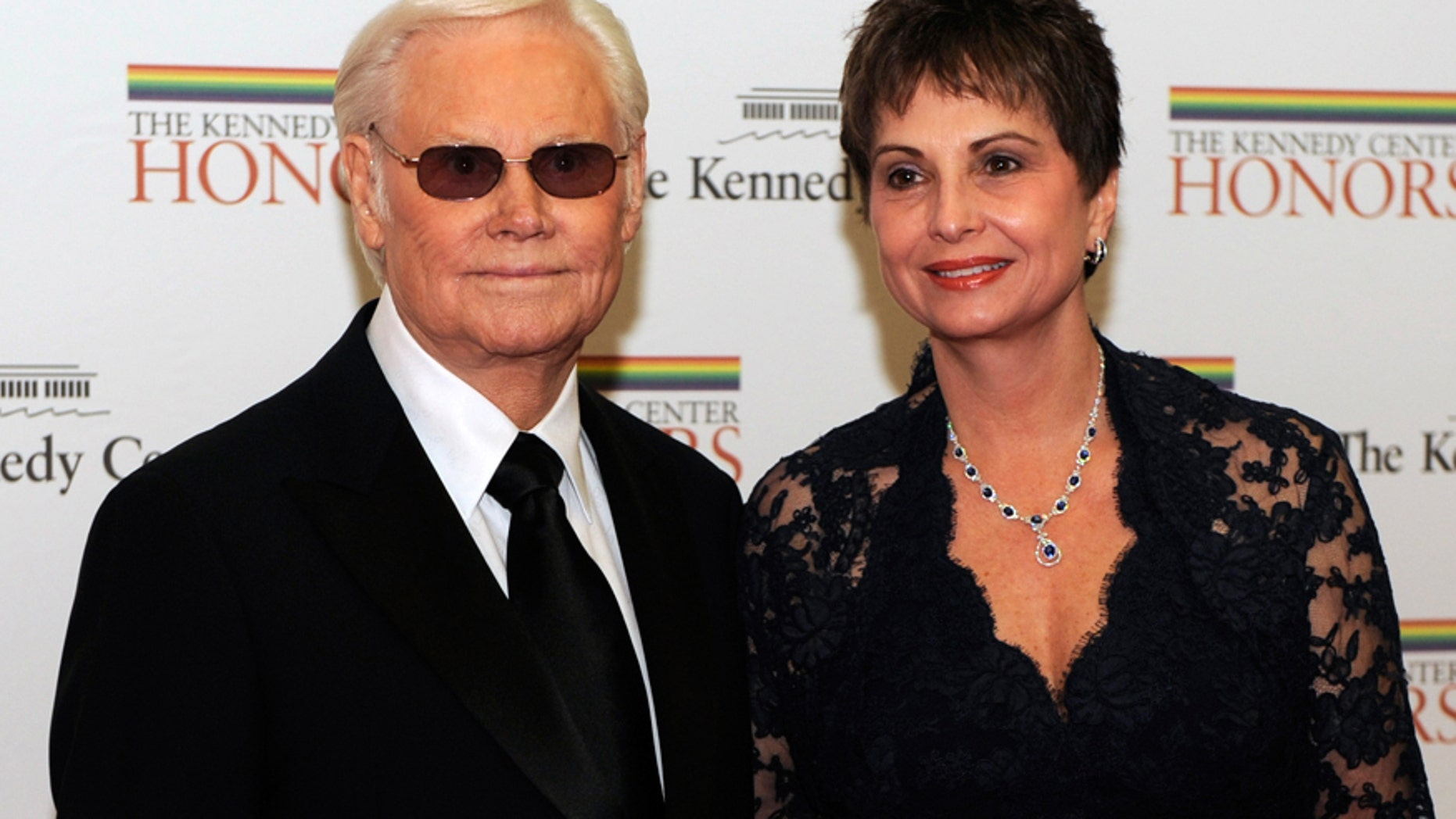 Country singer George Jones (L), a 2008 Kennedy Center Honoree, poses for photographers with his wife Nancy as they arrive for the 2008 Honors gala dinner at the US State Department in Washington December 6, 2008.