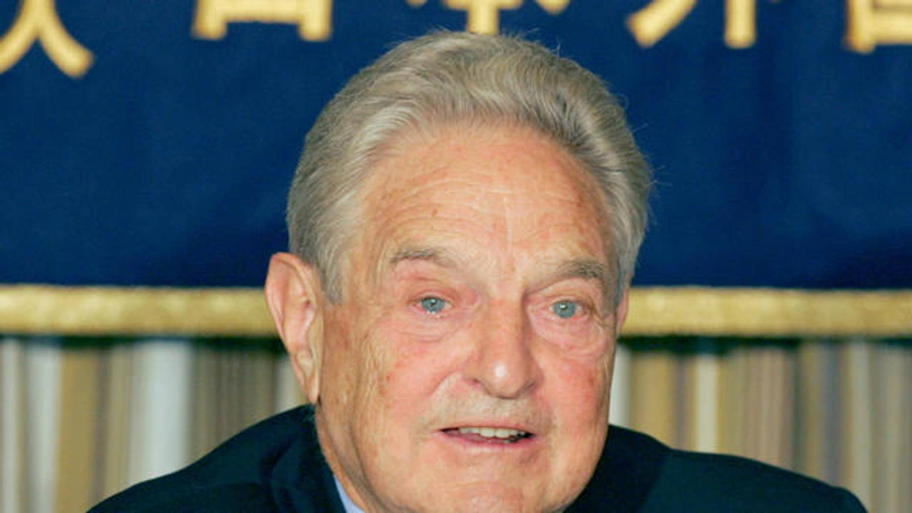 "Billionaire financier and philanthropist George Soros speaks to reporters at the Foreign Correspondents' Club of Japan in Tokyo Monday, Oct. 16, 2006. Soros said that China should allow its currency to appreciate in order to maintain economic stability. Shown at right on the table is a copy of the Japanese version of his latest book ""The Age of Fallibility."" (AP Photo/Koji Sasahara)"