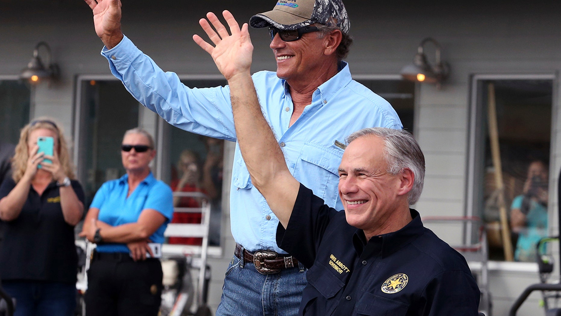 """In this Sept. 21, 2017, file photo, George Strait, left, and Texas Gov. Greg Abbott wave to the crowd in Rockport, Texas, during a visit with individuals affected by Hurricane Harvey. Strait leads a new tourism campaign for Hurricane Harvey-damaged Rockport and Fulton nearly 10 months after the storm devastated the area he sometimes calls home. Strait is part of the """"Find Yourself in Rockport-Fulton"""" radio and TV campaign to encourage tourists to return to the area hard-hit when Harvey made landfall in August."""
