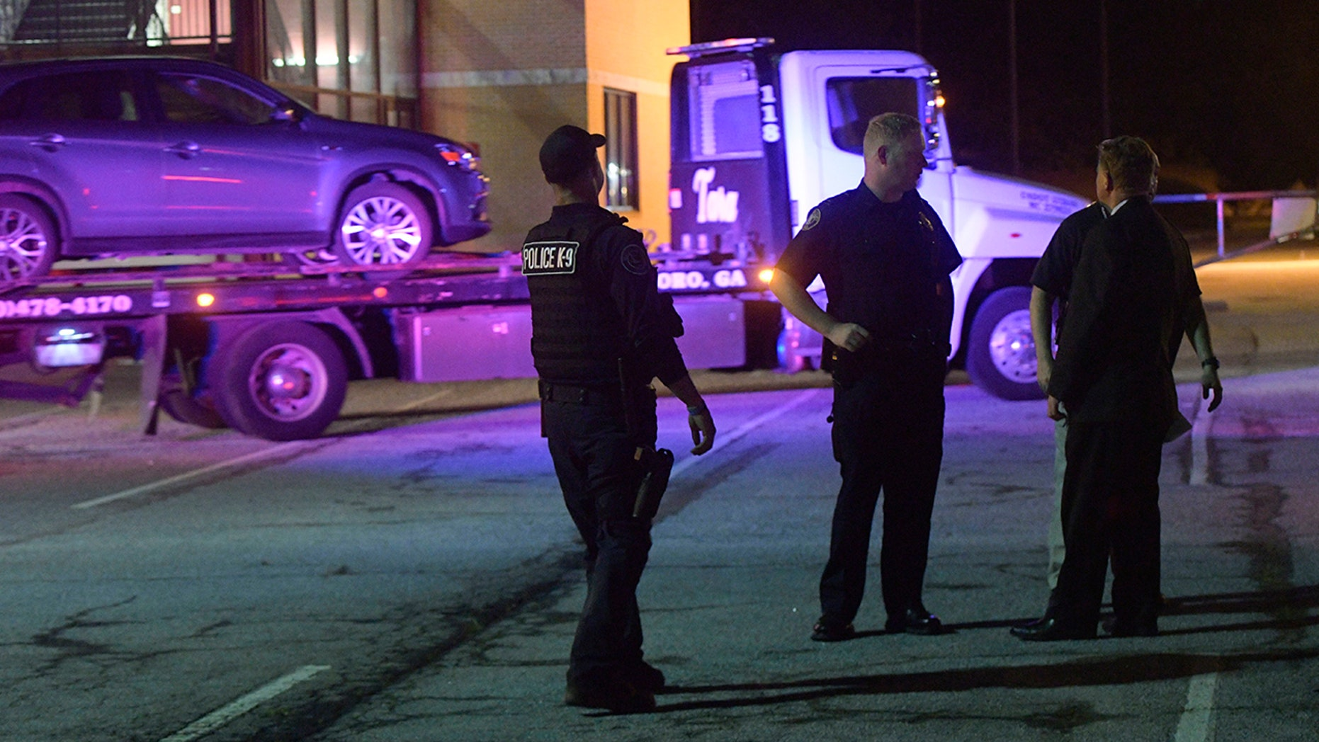 Law enforcement officers talk as a car is towed away in the Mt. Zion High School parking lot as part of an investigation into a shooting Friday, May 18, 2018, in Jonesboro, Ga.