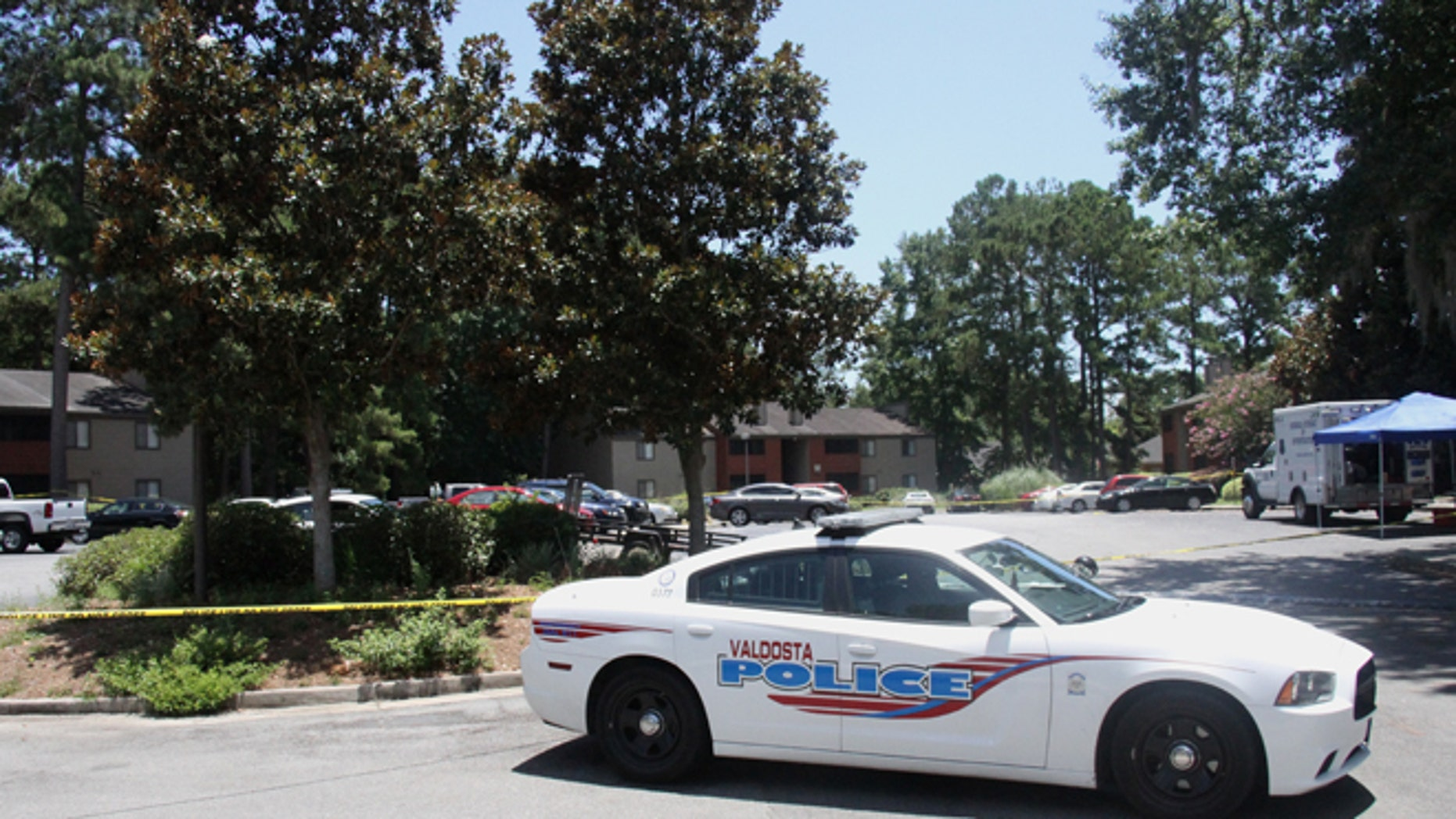 A police vehicle parks near the scene of an officer involved shooting, Friday, July 8, 2016, in Valdosta, Ga. A man who called 911 to report a car break-in Friday ambushed a south Georgia police officer dispatched to the scene, sparking a shootout in which both the officer and suspect were wounded, authorities said. Both are expected to survive.(Gabe Burns/The Daily Times via AP) MANDATORY CREDIT