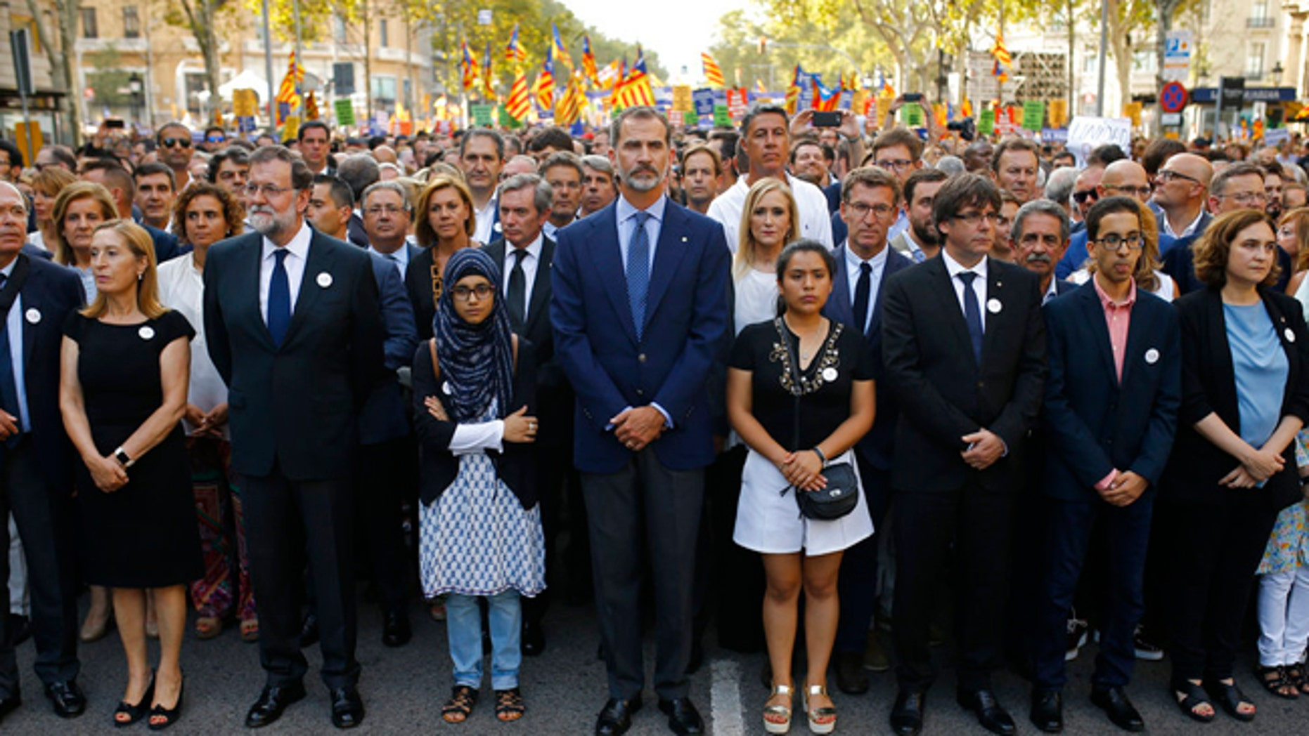 Spain's King Felipe, centre, Spain's Prime Minister Mariano Rajoy, 3rd left and Catalonia regional President Carles Puigdemont, 4th from right and other politicians take part in a demonstration condemning the attacks that killed 15 people last week in Barcelona, Spain, Saturday, Aug. 26, 2017.