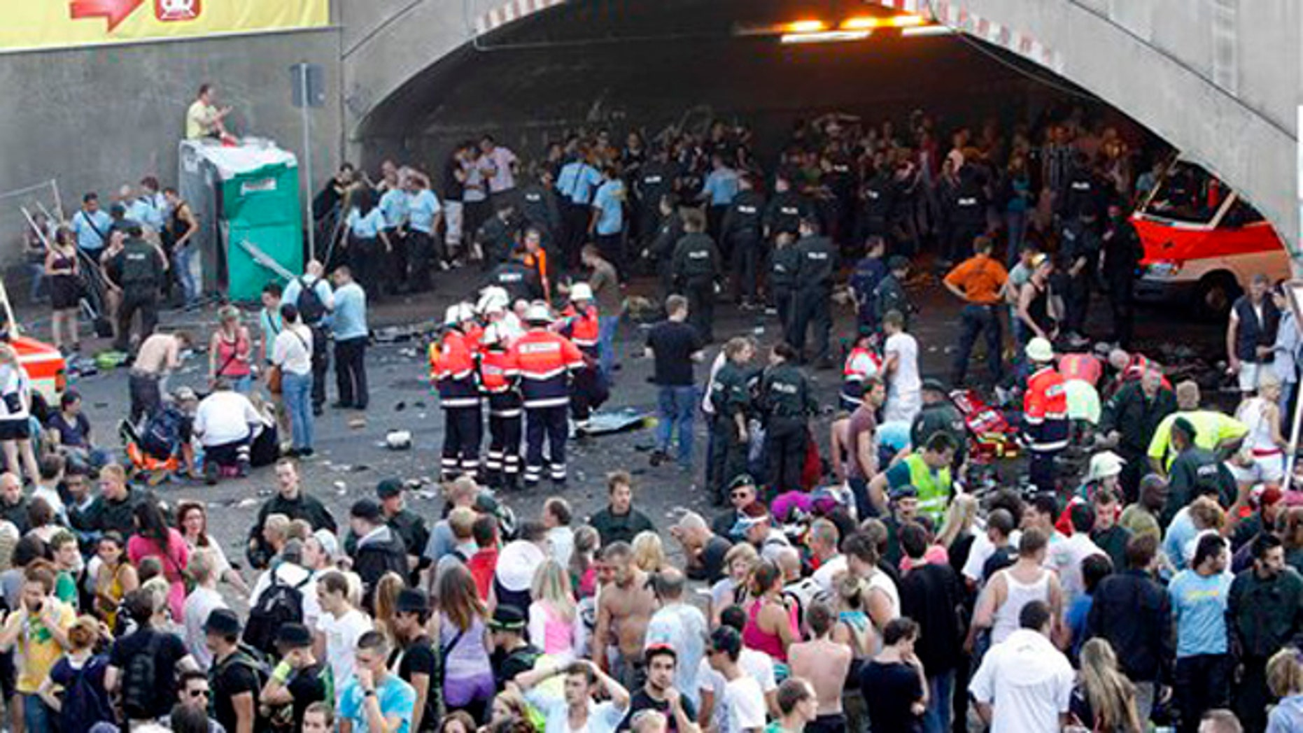 """Collapsed people get first aid after a panic on this year's techno-music festival """"Loveparade 2010"""" in Duisburg, Germany, on Saturday, July 24, 2010. German police say that 10 people were killed and 15 others injured when mass panic broke out in a tunnel at the Love Parade.  (AP Photo/dapd/Hermann J. Knippertz)"""