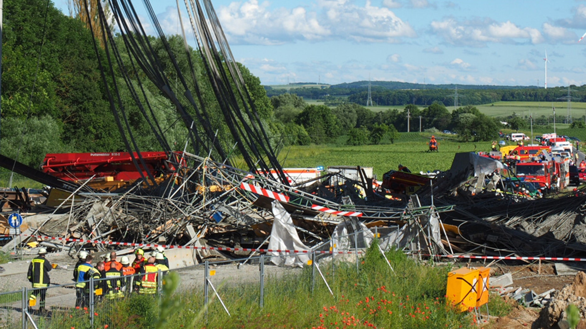 June 15, 2016: Firefighters stand near a collapsed scaffolding at a highway bridge near Werneck northern Bavaria, Germany.
