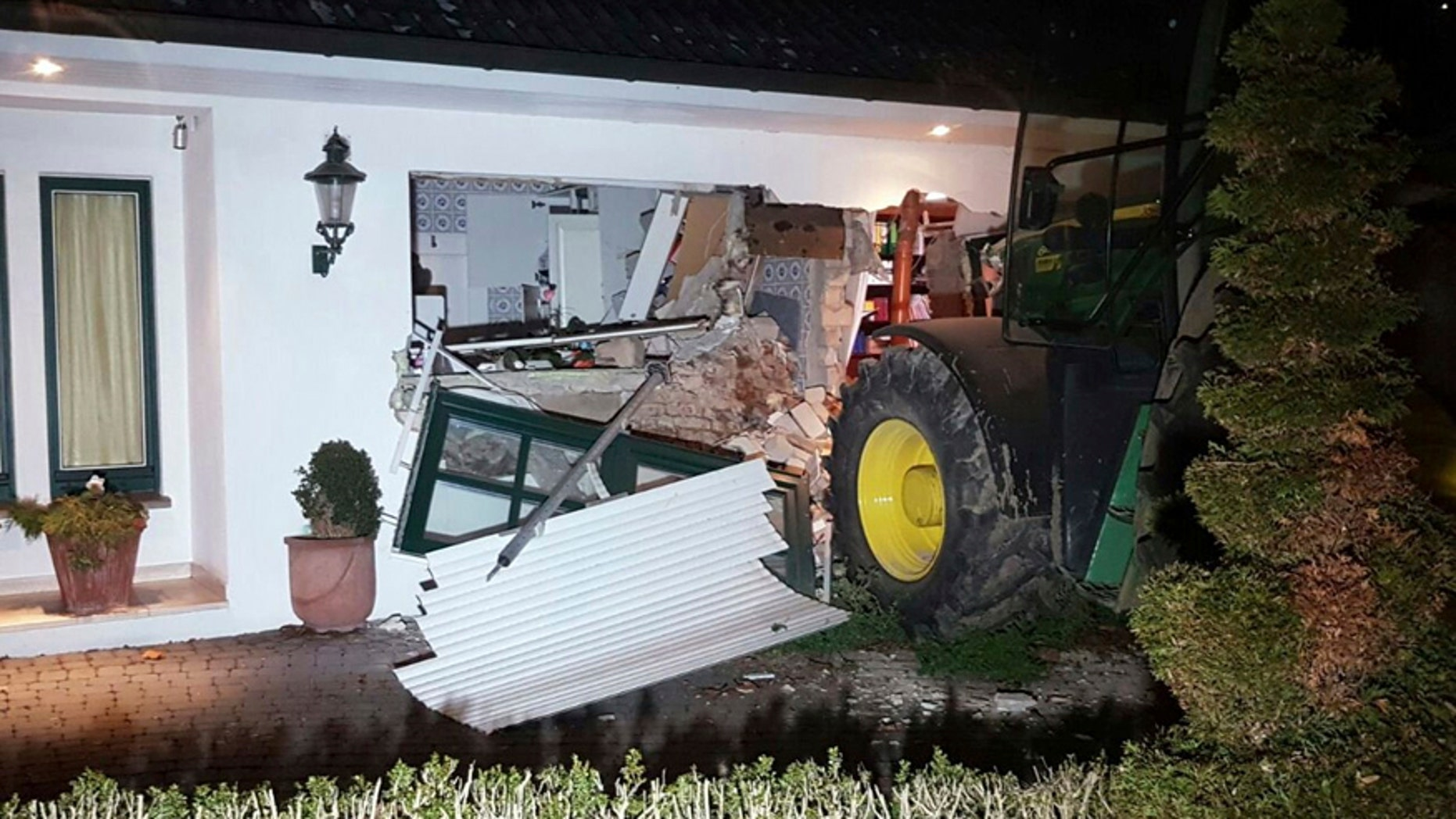 A tractor stands in front of a damaged house after it broke through the wall in Buende, north-western Germany, Thursday, Jan. 26, 2017. Unknown intruders steered the tractor into the house and broke through the wall in order to steal a safe. The residents were not injured. (Nord-West-Media TV/dpa via AP)