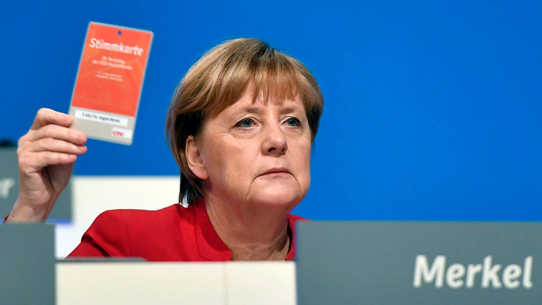 German Chancellor and Chairwomen of the CDU, Angela Merkel, holds an voting ticket during a party conference of the Christian Democratic Union (CDU) in Essen, Germany, Tuesday, Dec. 6, 2016. Chancellor Angela Merkel has won a new two-year term as leader of Germany's main conservative party after she won 89.5 percent of delegates' votes at a party congress. (AP Photo/Martin Meissner)