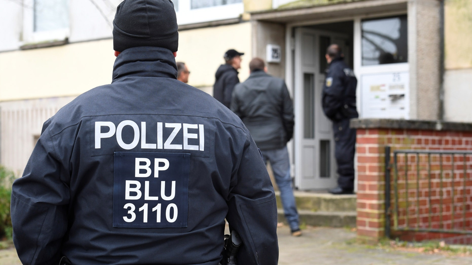 Police conduct a raid in front of a residential building in Schwerin, Germany in October.