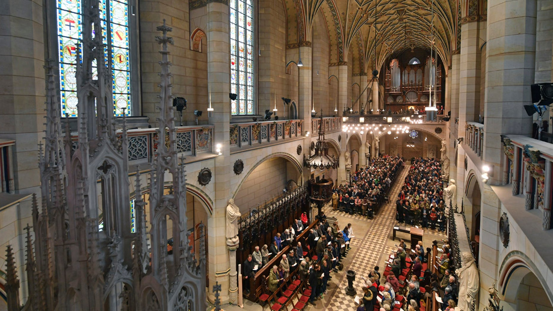 Visitors of the service sit in the All Saints' Church or Castle Church  in Wittenberg, Germany, Tuesday Oct. 31,  2017.  German leaders  will mark the 500th anniversary of the day Martin Luther is said to have nailed his theses challenging the Catholic Church's practice of selling indulgences to a church door, a starting point of the Reformation. (Hendrik Schmidt/dpa via AP)
