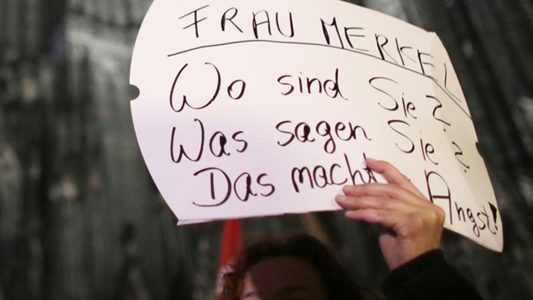 "A woman protests against sexism outside the cathedral in Cologne, Germany, Tuesday Jan. 5, 2016. Poster reads "" Mrs. Merkel. Where are you? What do you say? It's scary."" (Associated Press)"