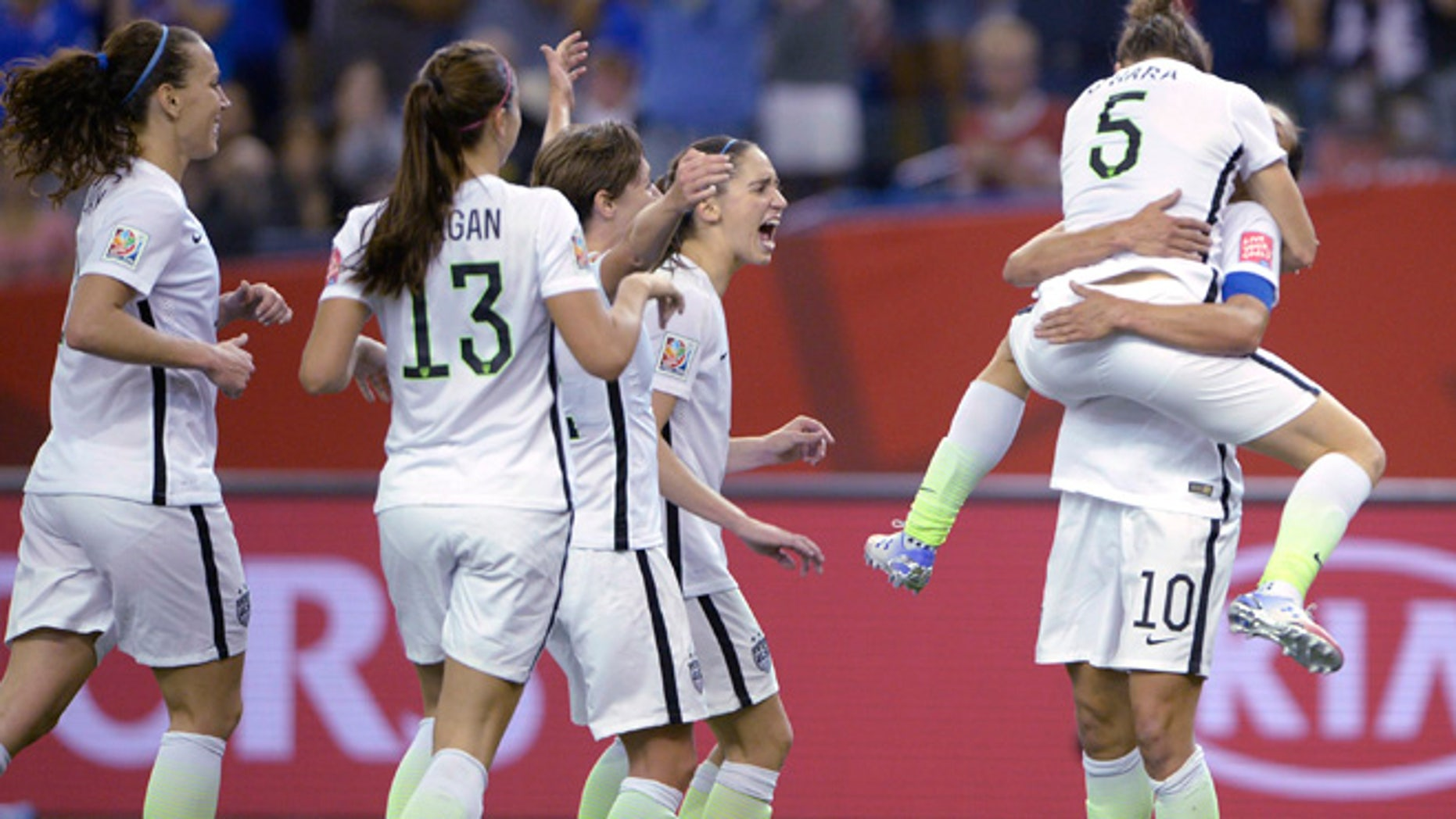 June 30, 2015: United States' Kelly O'Hara (5) jumps into the arms of Carli Lloyd after O'Hara scored against Germany during the second half of a semifinal in the Women's World Cup soccer tournament in Montreal, Canada. (AP)