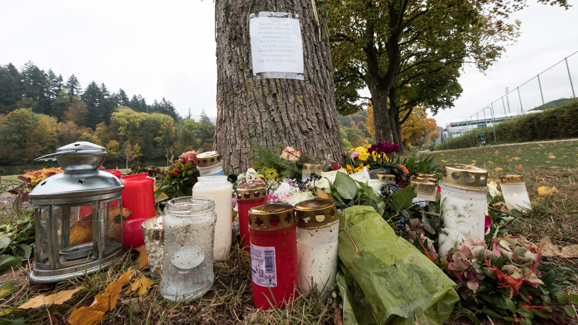 Oct. 21, 2016:  Flowers and candles sit in front of a tree close to the Dreisam river in Freiburg, Germany, where the body of a student was found. A 17-year-old Afghan migrant, who entered Germany last year as an unaccompanied minor, was arrested Friday in connection with the killing.