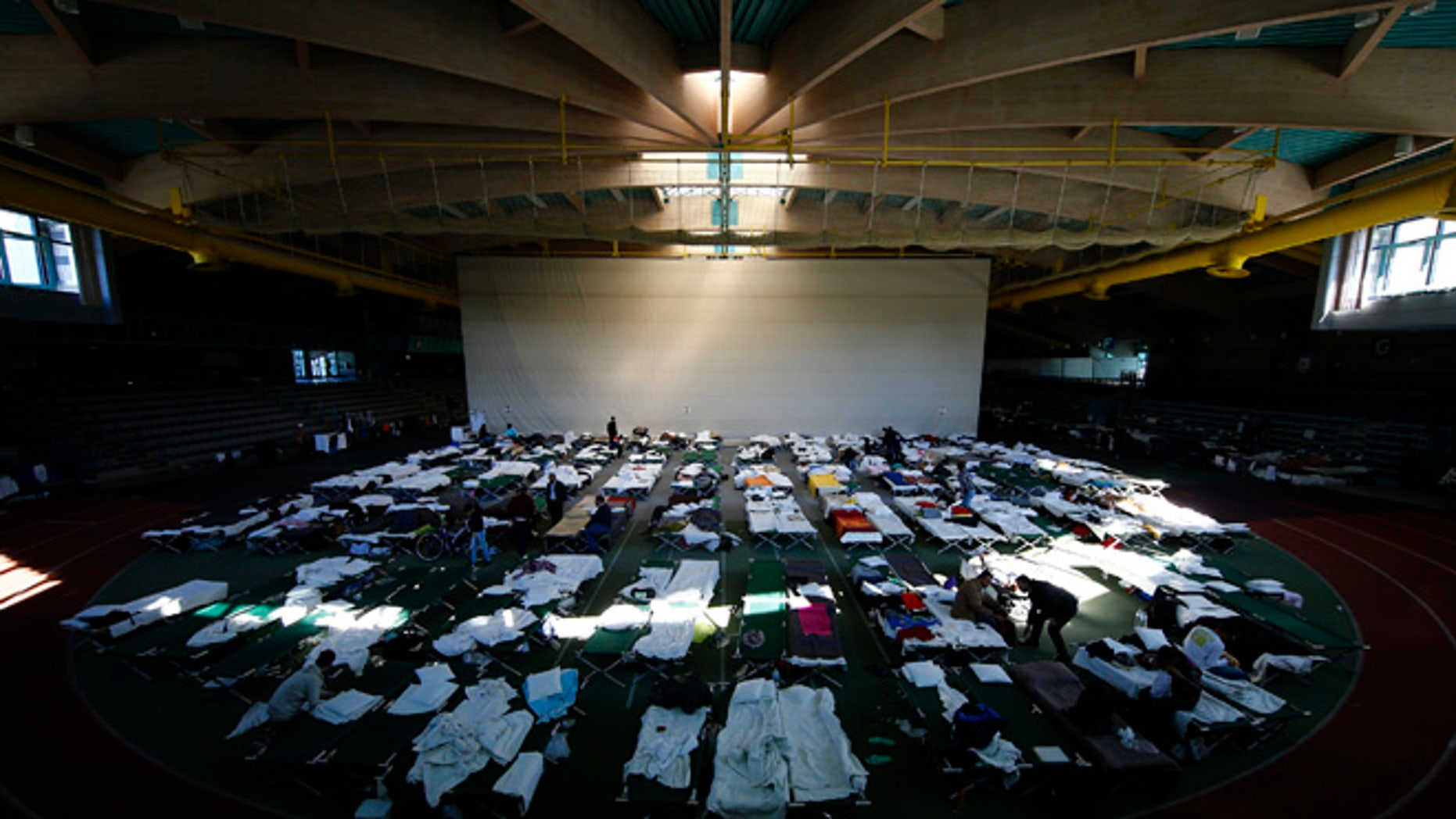 October 1, 2015: Migrants rest at a temporary shelter in a sports hall in Hanau, Germany.