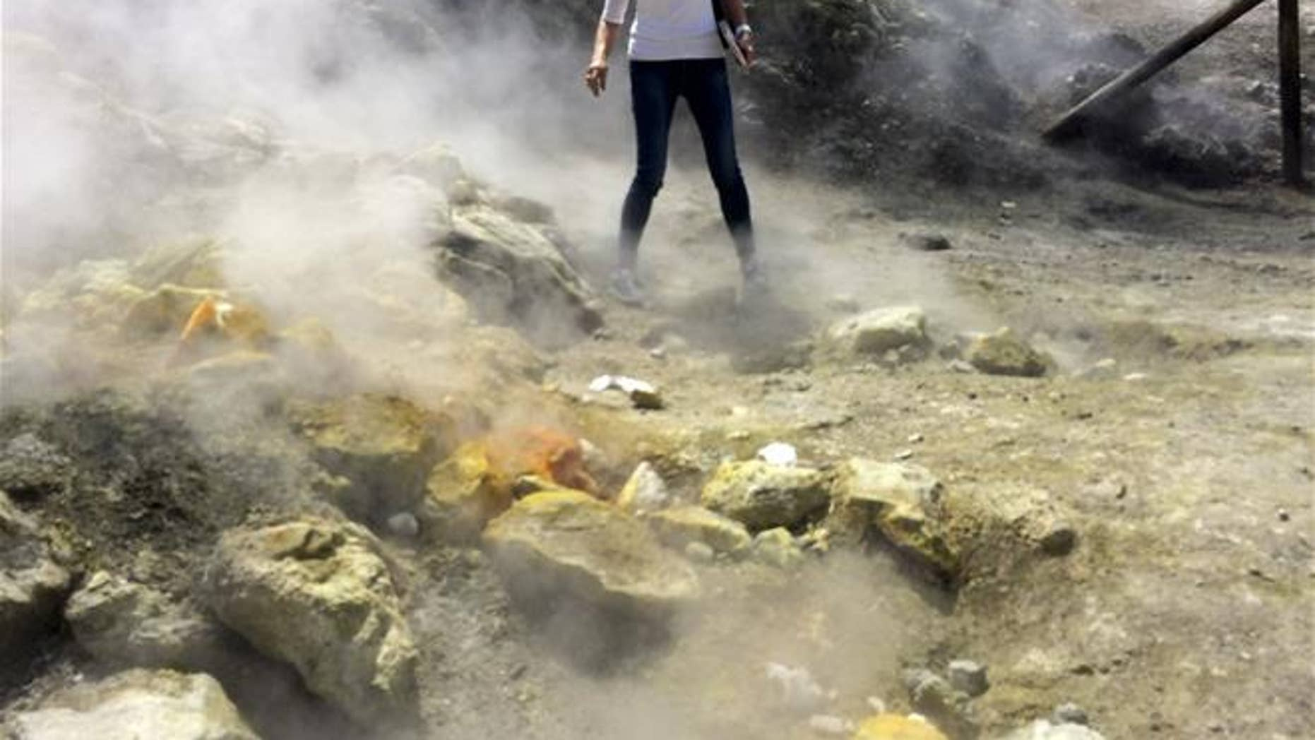 A woman takes a close look at a steaming fumarola at the Solfatara crater bed in Italy's Campi Flegrei last April.   (AP Photo/Frances D'Emilio)