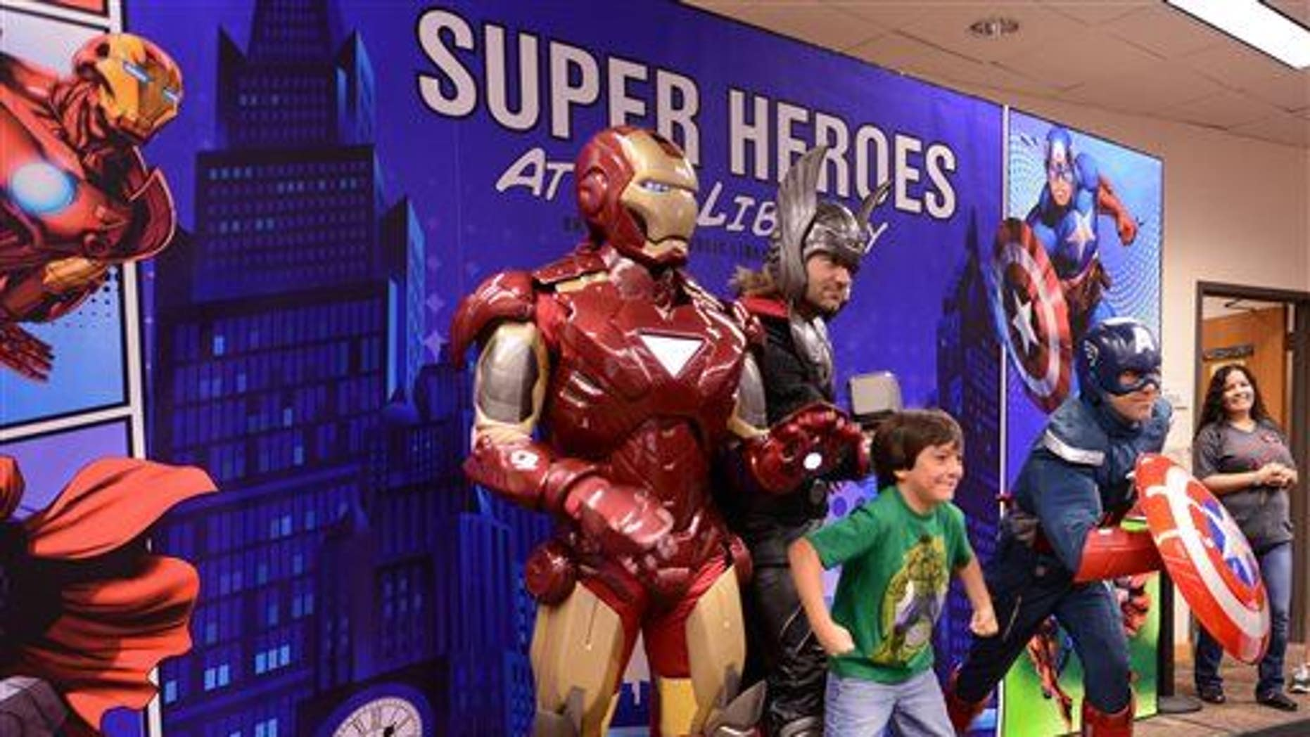 A boy strikes a pose with three superheroes in this file photo.