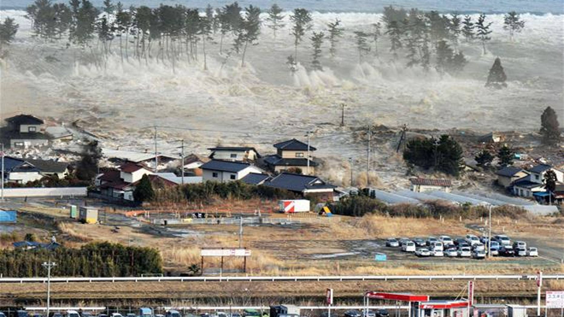 In this March 11, 2011 aerial photo, a tsunami hit Natori, Miyagi Prefecture, northeastern Japan. (Kyodo News via AP, File)