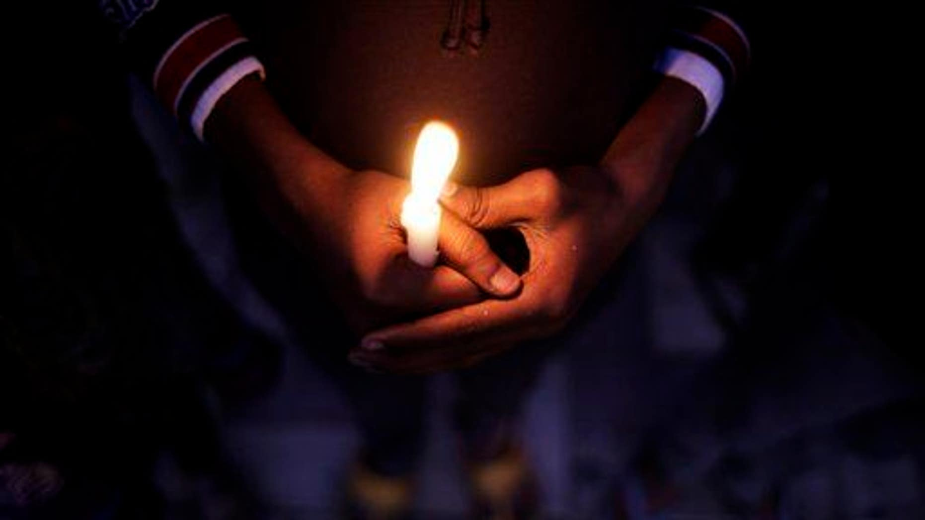An Indian child holds a candle during a candlelight vigil in New Delhi, India, in this 2014 file photo.