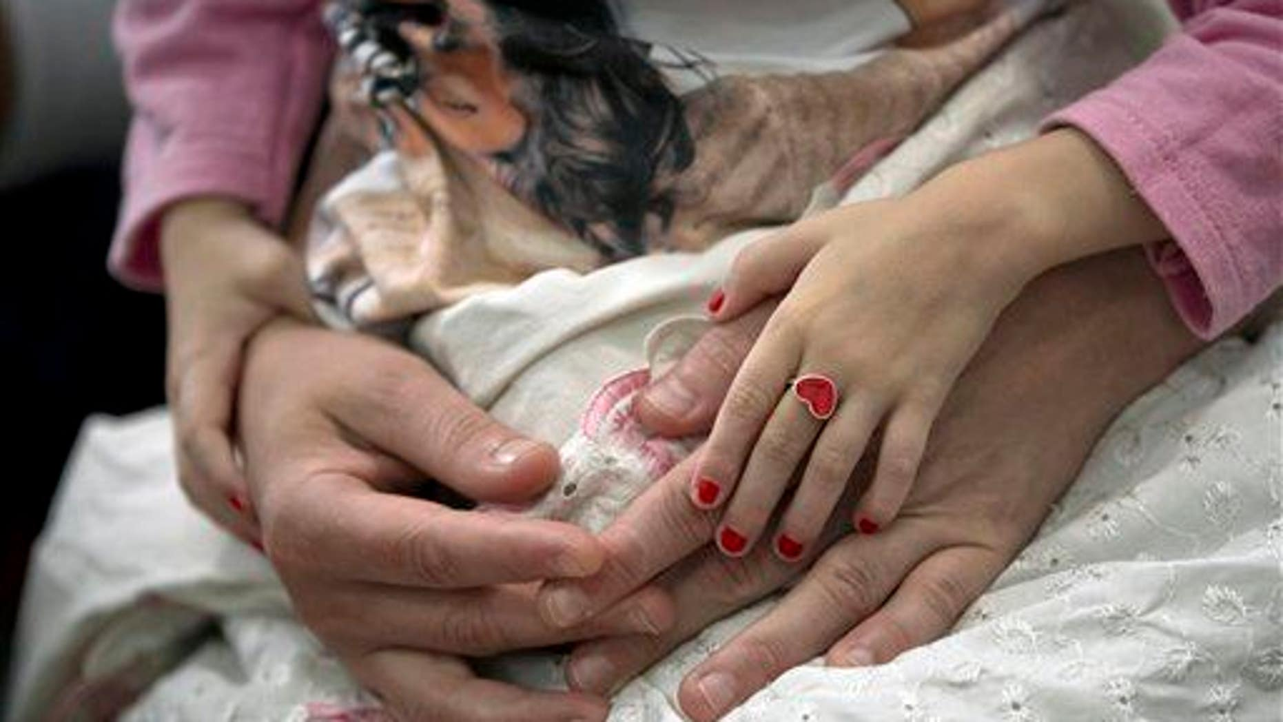 A young girl holds her mother's hands in this file photo.