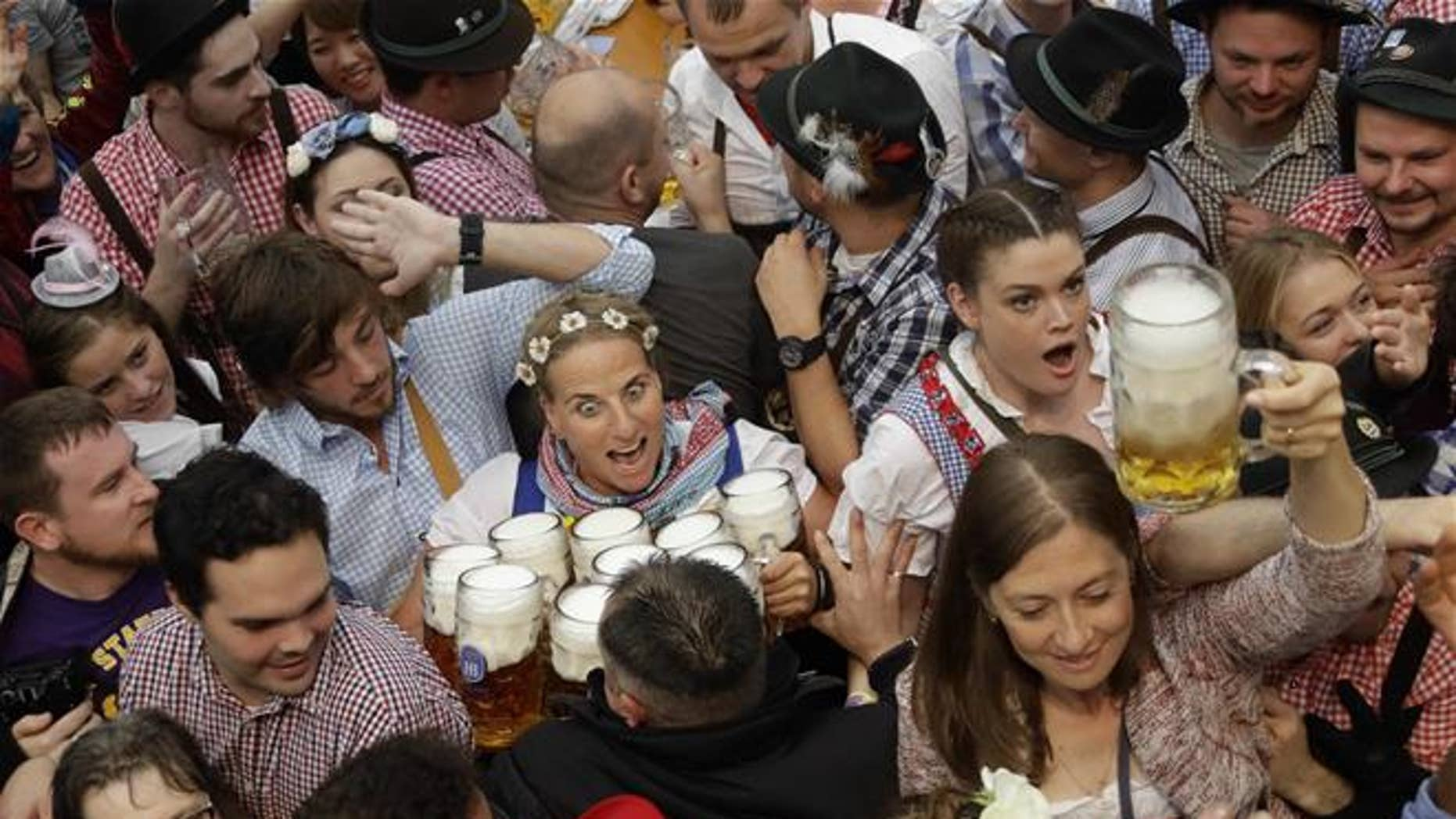 FILE - In this Saturday, Sept. 17, 2016 file photo a waitress is surrounded by visitors during the opening ceremony of the 183rd Oktoberfest beer festival in Munich, southern Germany.