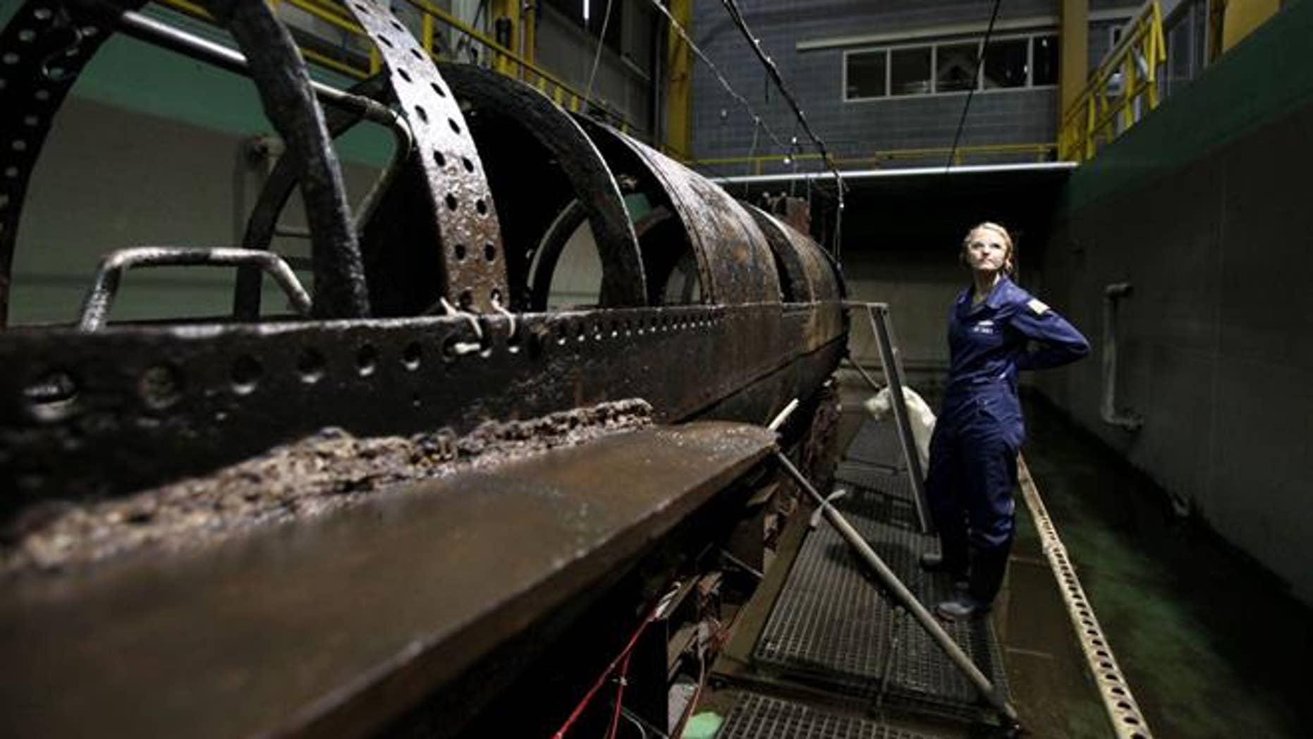 Conservator Anna Funke stands next to the HL Hunley at the Warren Lasch Conservation Center on Wednesday. (Michael Pronzato/The Post And Courier via AP)