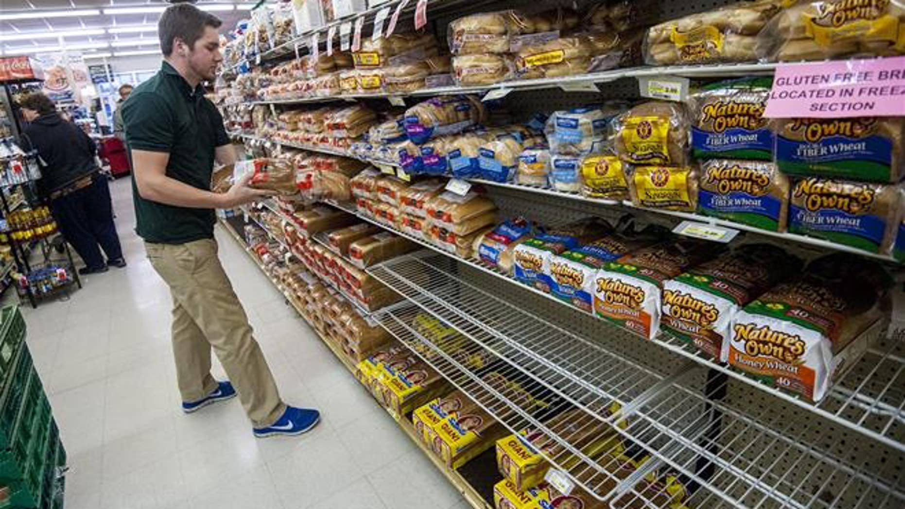 Bridgewater College junior communication major Jonah Barnhart, of Culpepper, Va., a floor stocker at Bridgewater Foods, stocks the bread aisle on Wednesday, Jan. 20, 2015, in Bridgewater, Va.