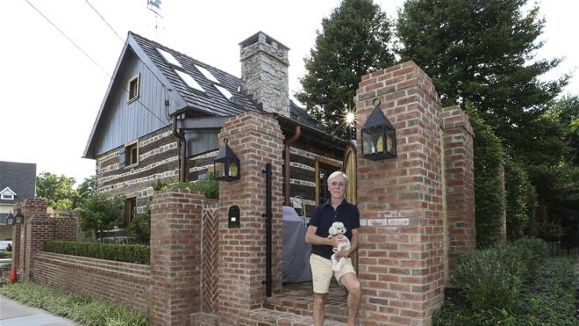Jude Plum, with his dog, at his 300-year-old log home in Bryn Mawr, Pa.