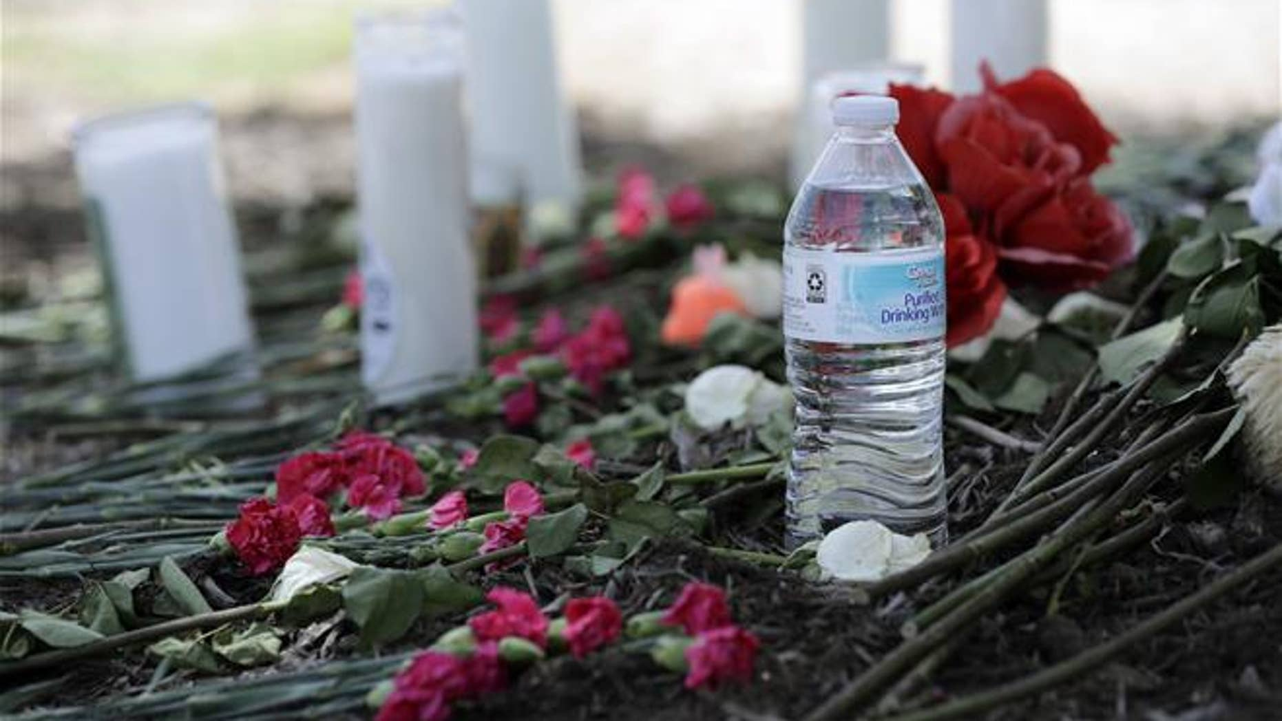 A bottle of water, flowers, candles and stuffed animals help form a makeshift memorial in the Walmart parking lot.
