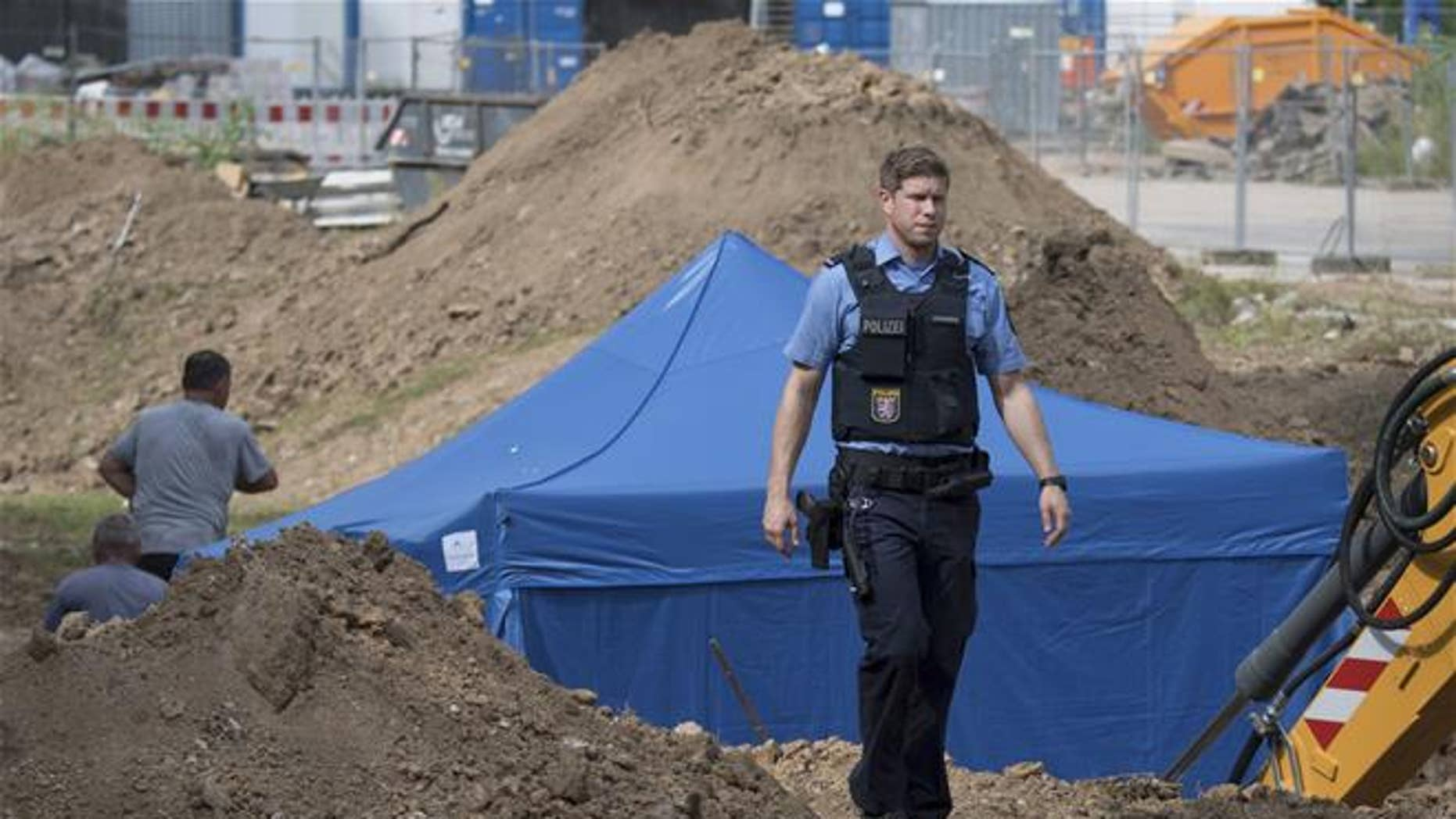In this photo taken Wednesday, Aug. 30, 2017 in Frankfurt, Germany, a police officer passes a blue tent that was set up over a bomb of a type dropped by British bombers during World War II.