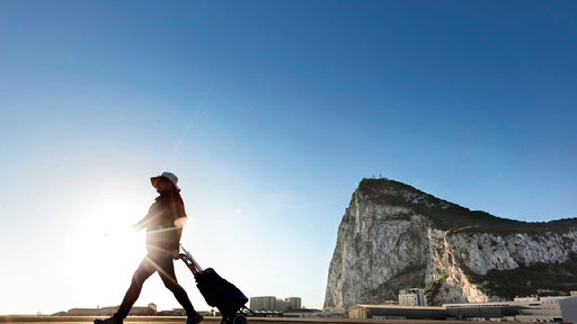 A woman walks on the Spanish side of the border between Spain and the British overseas territory of Gibraltar with the Rock as a background, in La Linea de la Concepcion, Southern Spain.