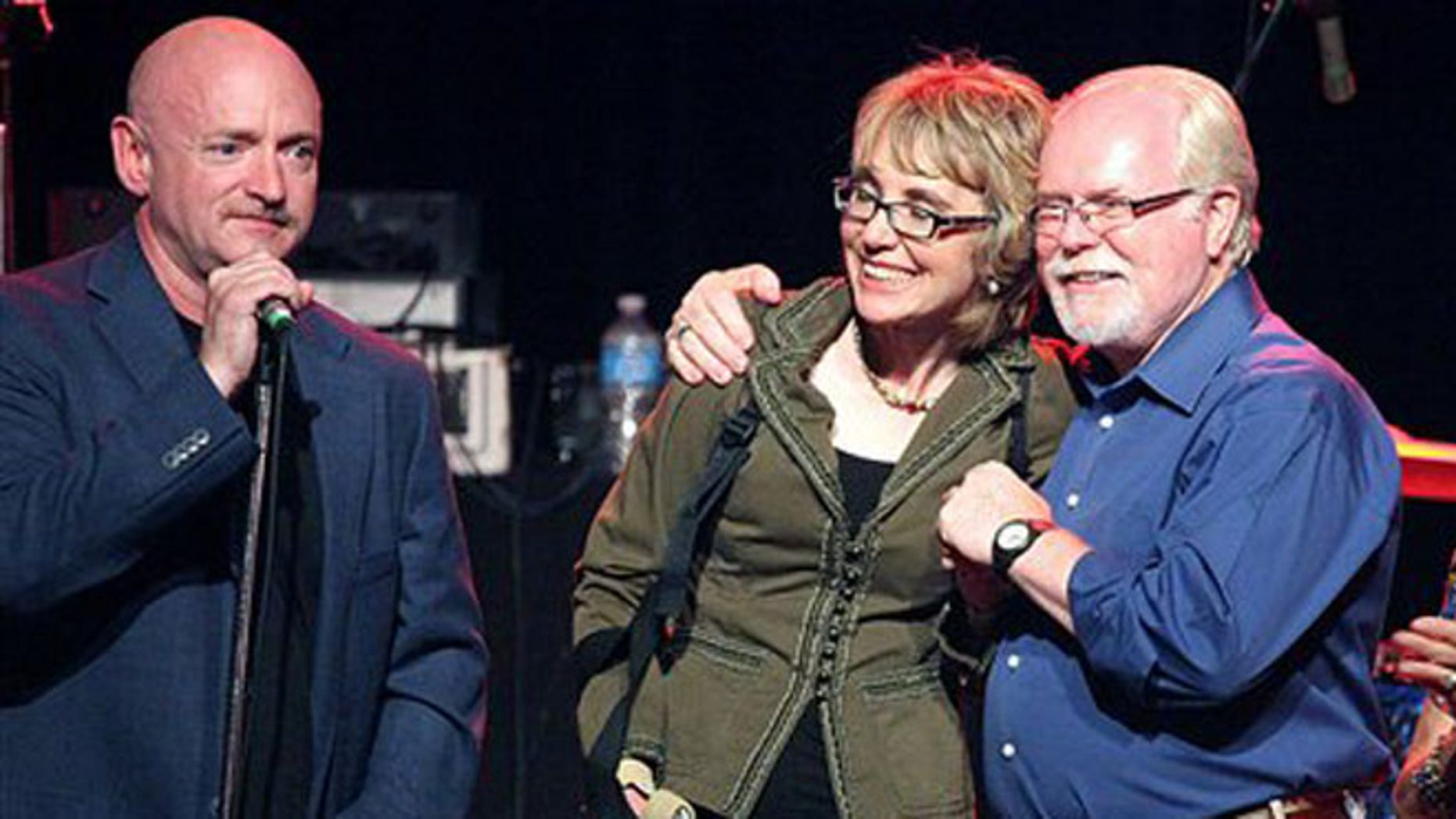 June 9, 2012: From left, Gabrielle Giffords' husband Mark Kelly, Giffords and congressional candidate Ron Barber gather during a get-out-the-vote rally at the Rialto Theater in downtown Tucson, Ariz.