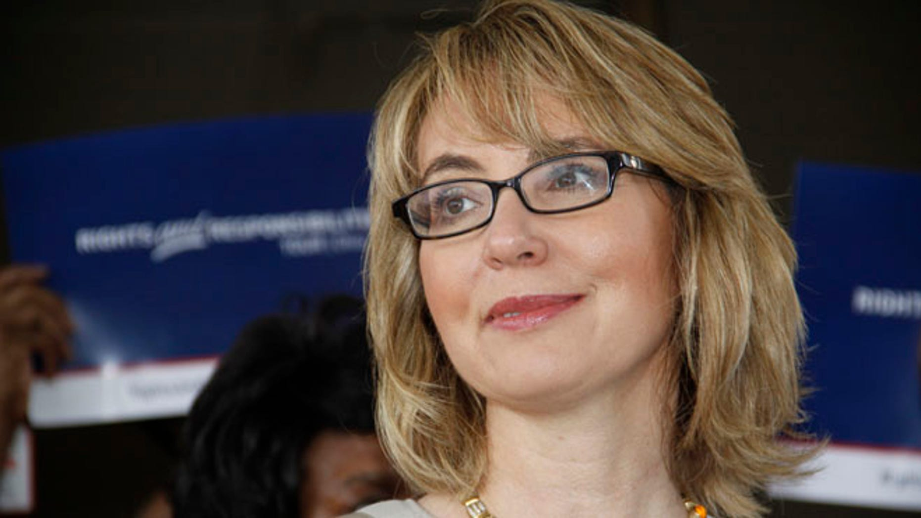 July 4, 2013: Former U.S. Rep. Gabrielle Giffords talks to supporters before she and husband, former astronaut Mark Kelly, take part in a parade in Northside, a suburb of Cincinnati.